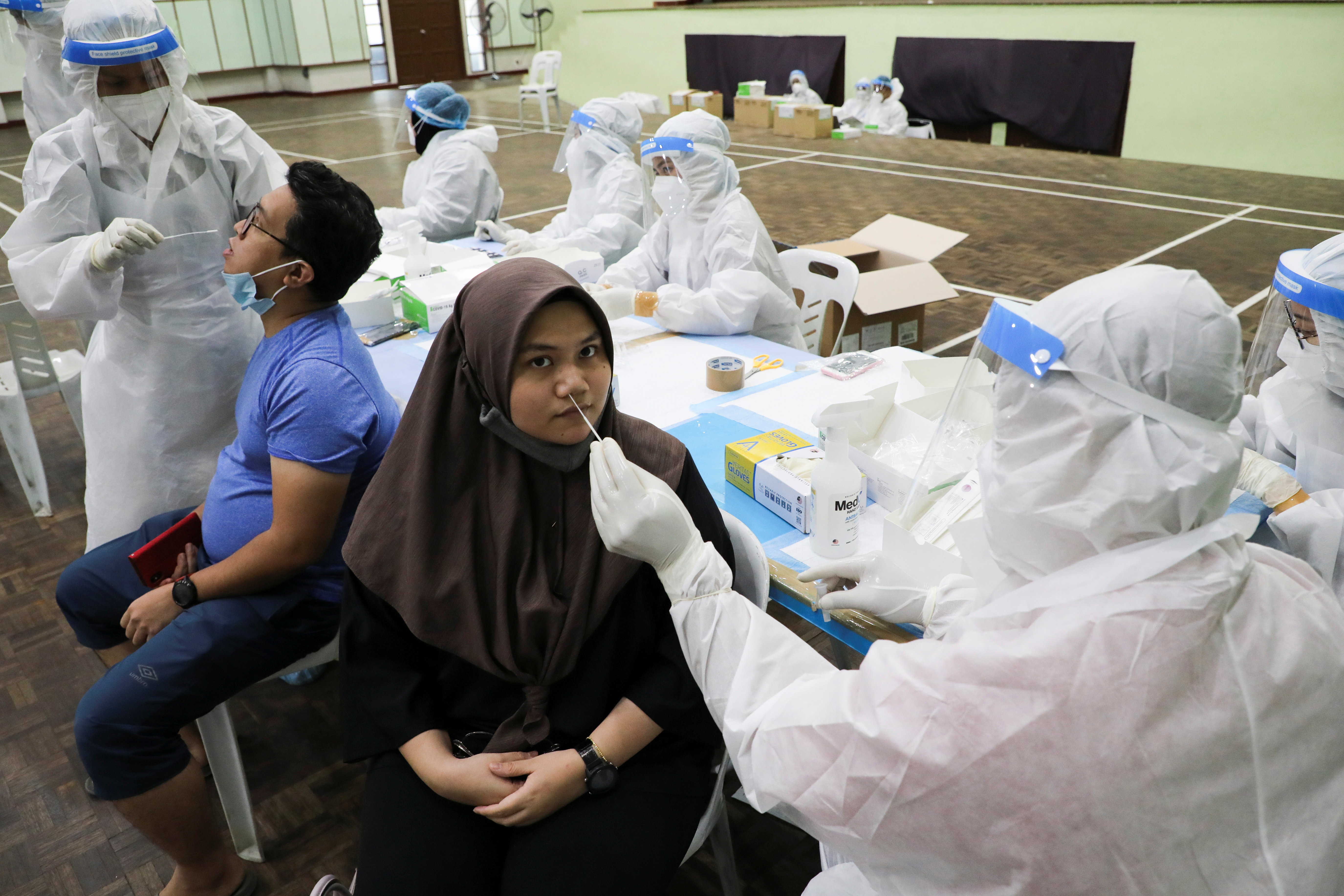 Medical workers collect swab samples from people to be tested for the coronavirus disease (COVID-19) in Kuala Lumpur, Malaysia, May 11, 2021. REUTERS/Lim Huey Teng