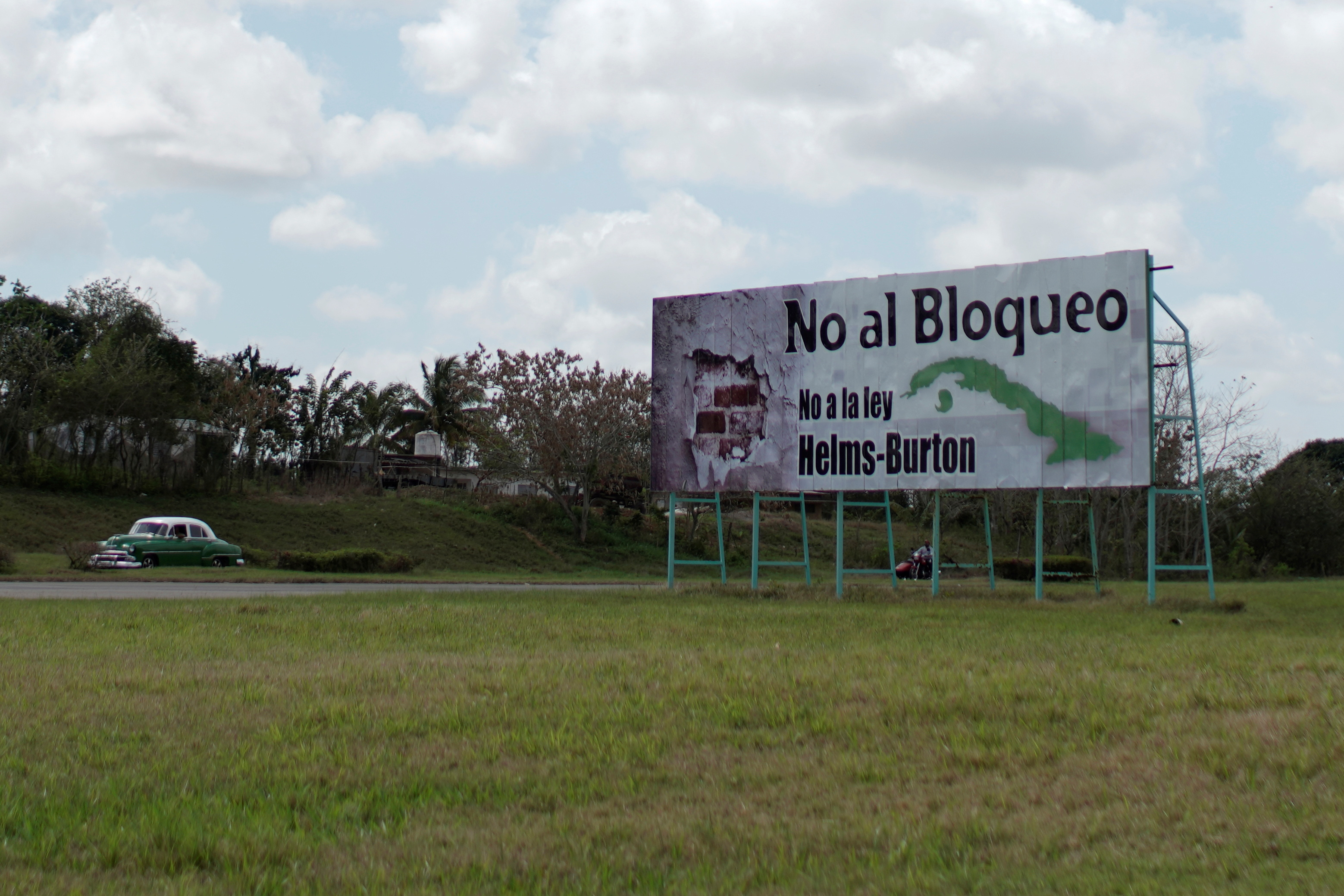 A vintage car passes by a billboard which reads in Spanish