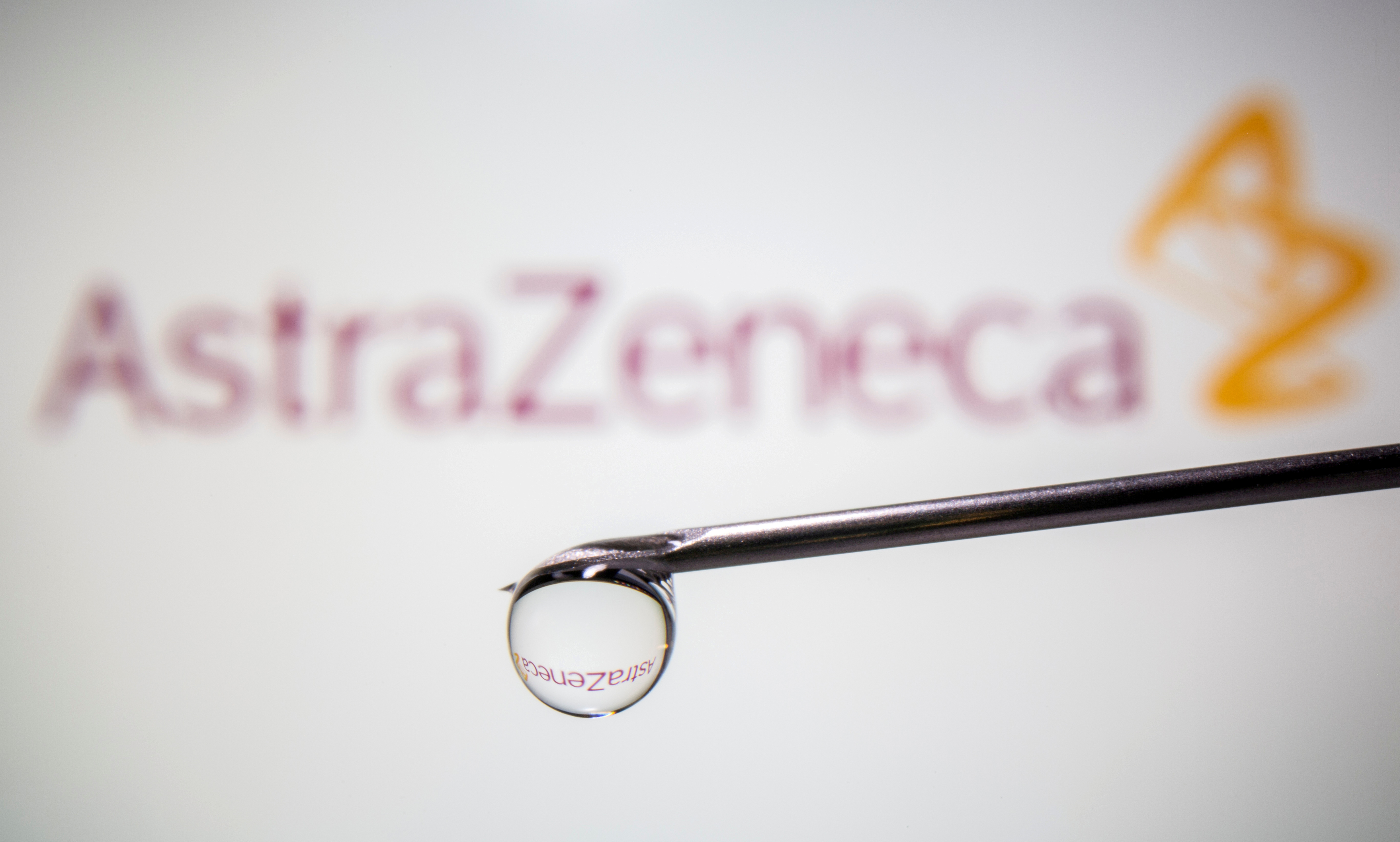 AstraZeneca's logo is reflected in a drop on a syringe needle in this illustration taken November 9, 2020. REUTERS/Dado Ruvic/Illustration