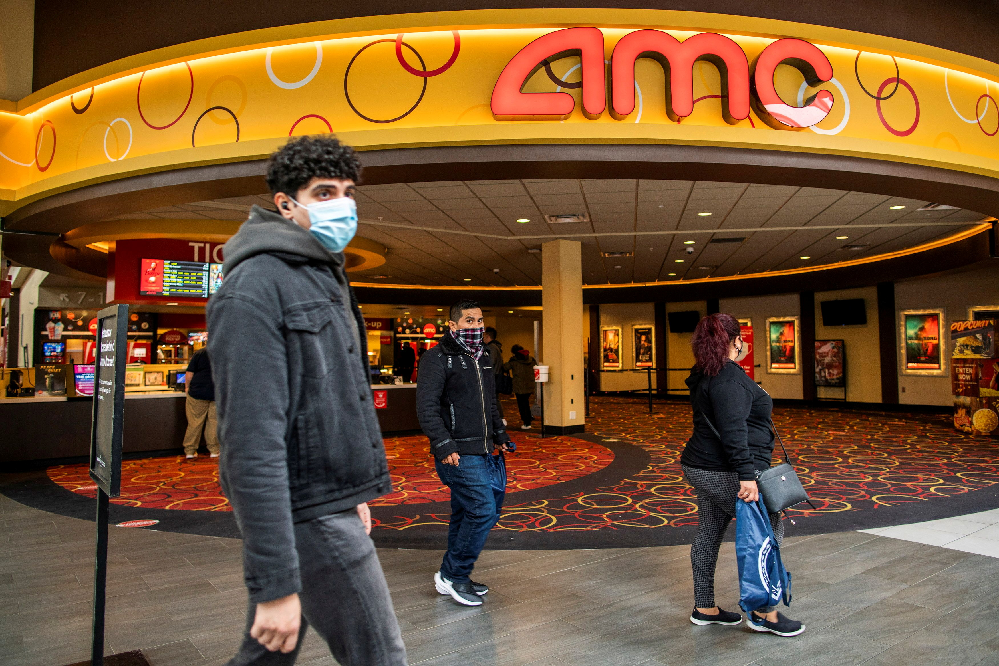 People wear face masks as they walk by a movie theater during the coronavirus disease (COVID-19) pandemic in Newport, New Jersey, U.S., April 2, 2021. REUTERS/Eduardo Munoz/File Photo