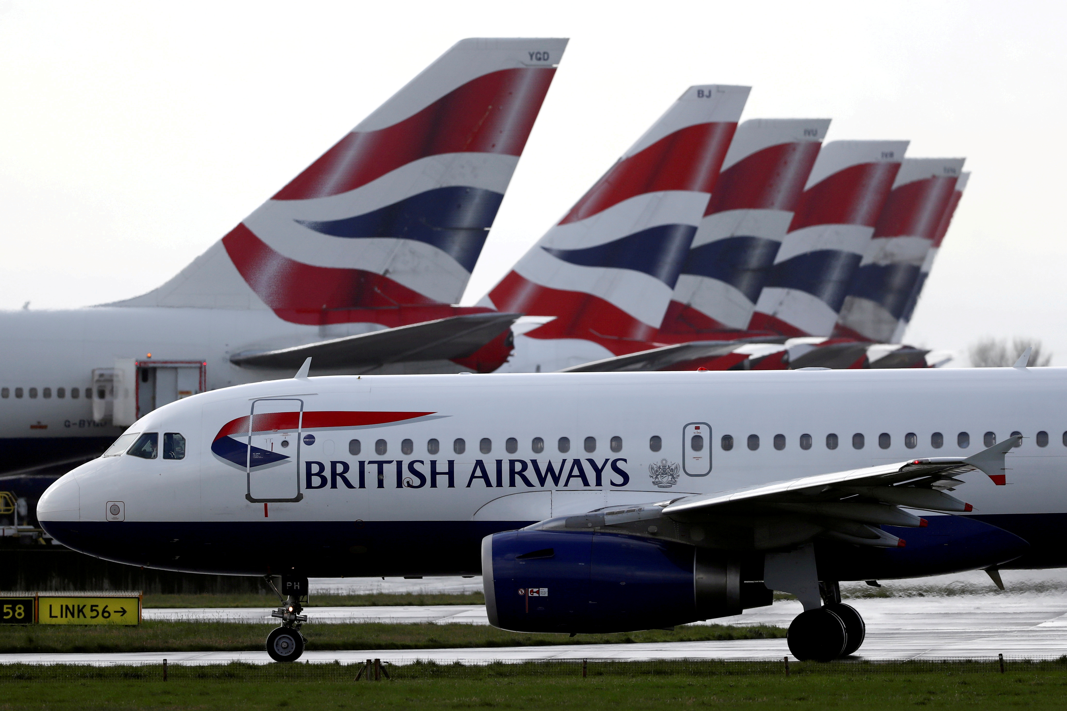 A British Airways plane taxis past tail fins of parked aircraft near Terminal 5 at Heathrow Airport in London, Britain, March 14, 2020. REUTERS/Simon Dawson
