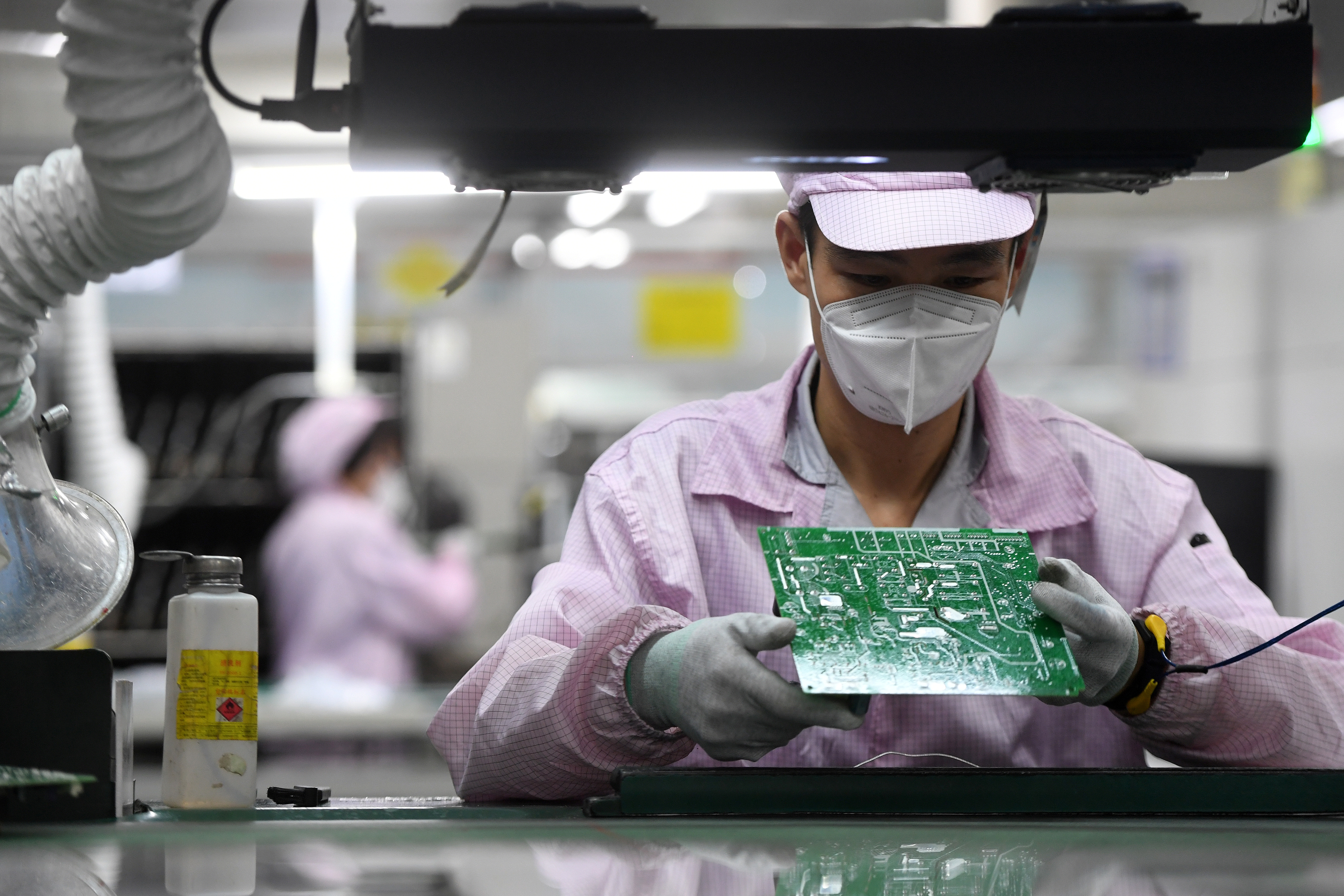 An employee inspects a circuit board on the controller production line at a Gree factory, following the coronavirus disease (COVID-19) outbreak in Wuhan, Hubei province, China August 16, 2021. China Daily via REUTERS