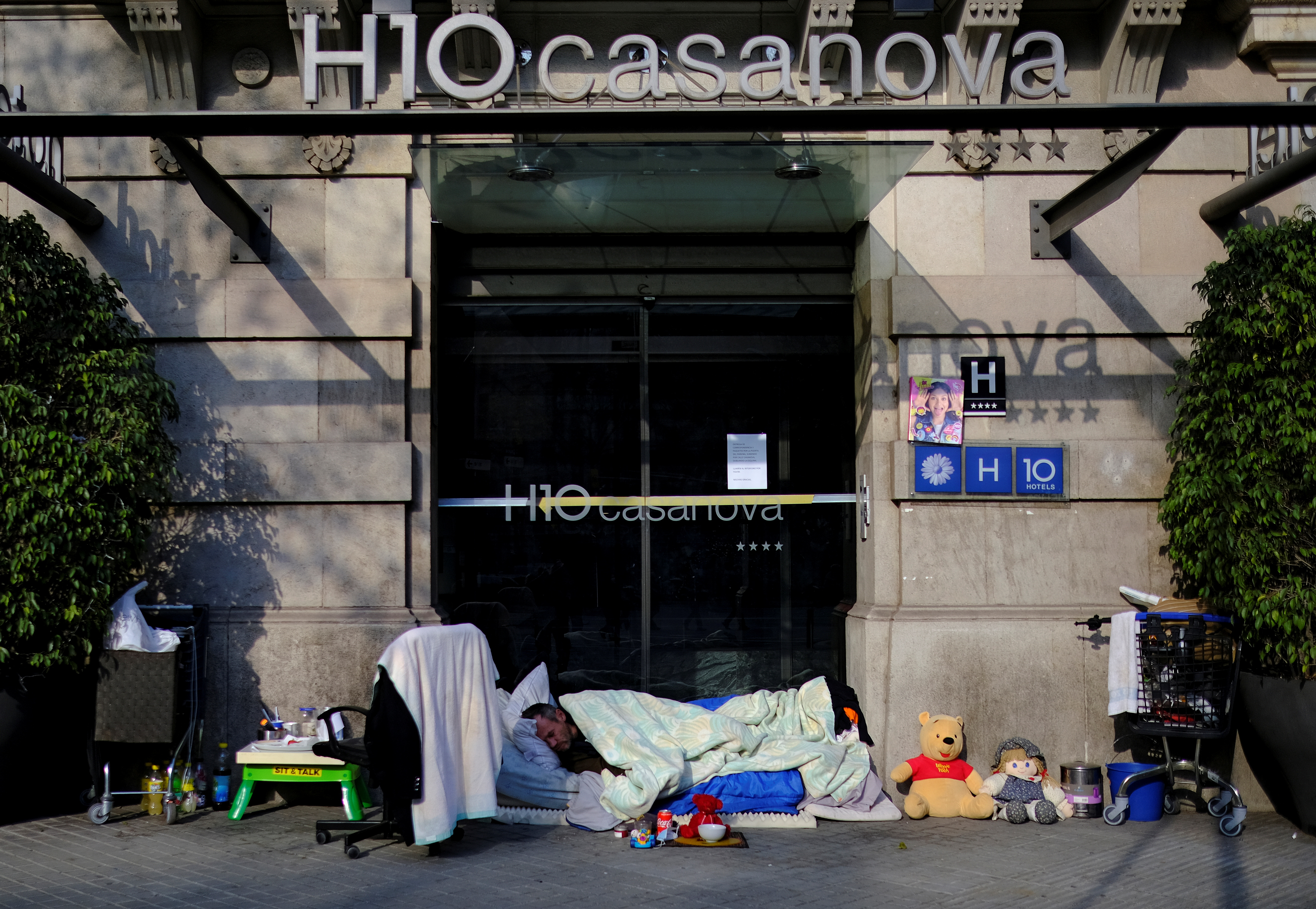 A homeless man sleeps on a mattress next to his belongings at the entrance of a closed hotel, after Catalonia's government imposed new restrictions in an effort to control the outbreak of the coronavirus disease (COVID-19) in Barcelona, Spain January 6, 2021. REUTERS/Nacho Doce