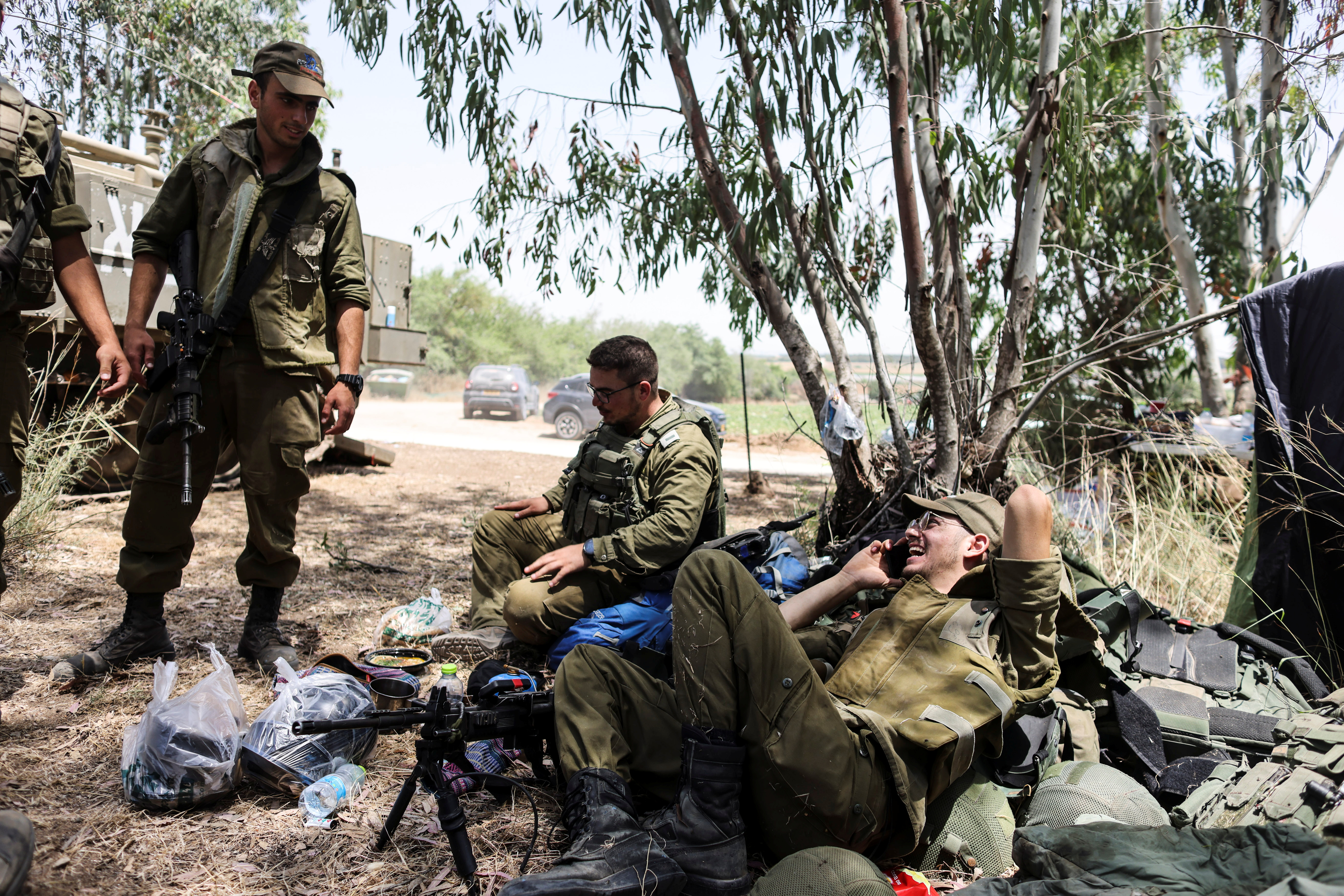 Israeli soldiers sit together in a field near the border between Israel and the Gaza Strip, on its Israeli side, following Israel-Hamas truce May 21, 2021. REUTERS/Ronen Zvulun