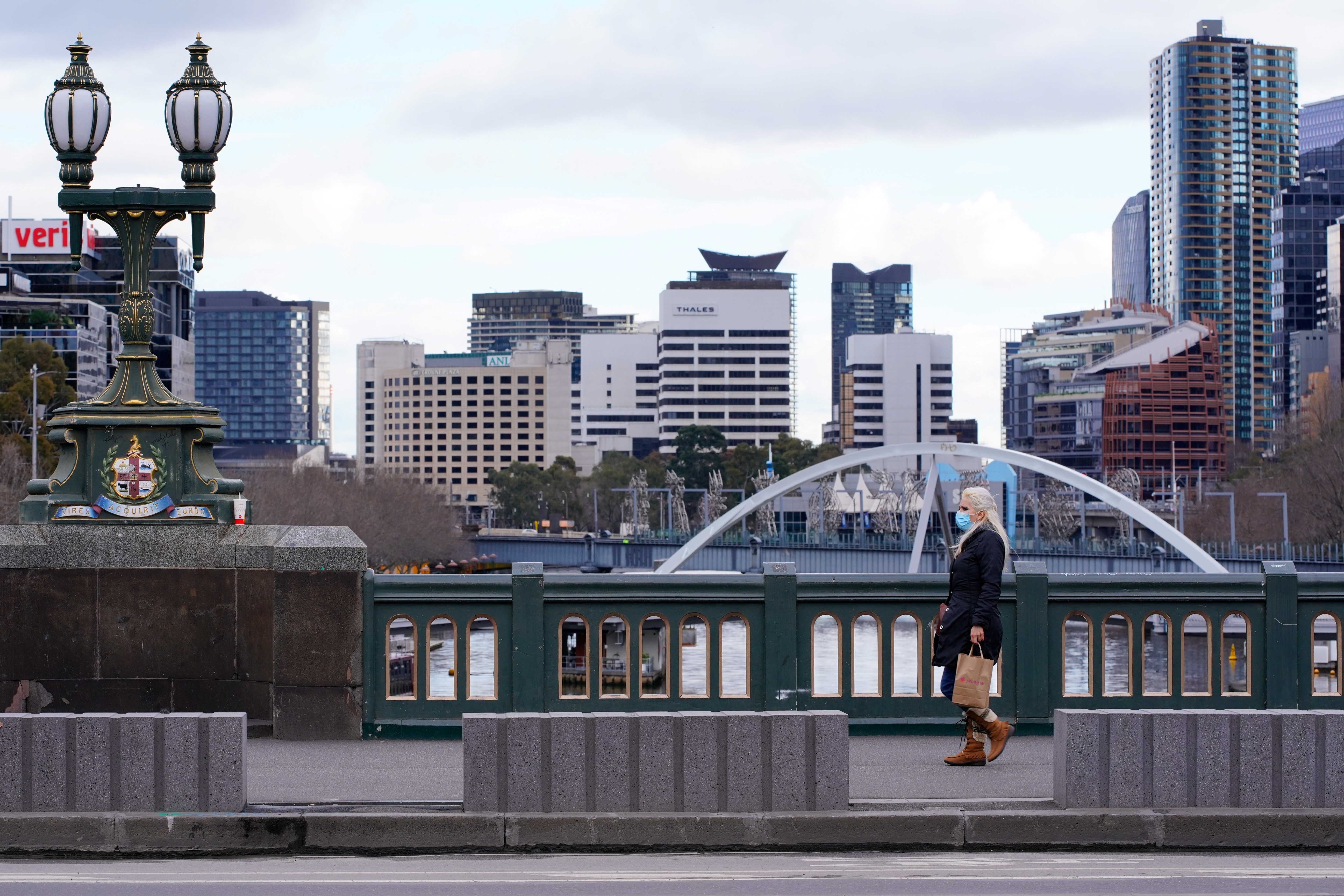 A lone woman, wearing a protective face mask, walks across an unusually quiet city centre bridge on the first day of a lockdown as the state of Victoria looks to curb the spread of a coronavirus disease (COVID-19) outbreak in Melbourne, Australia, July 16, 2021.  REUTERS/Sandra Sanders