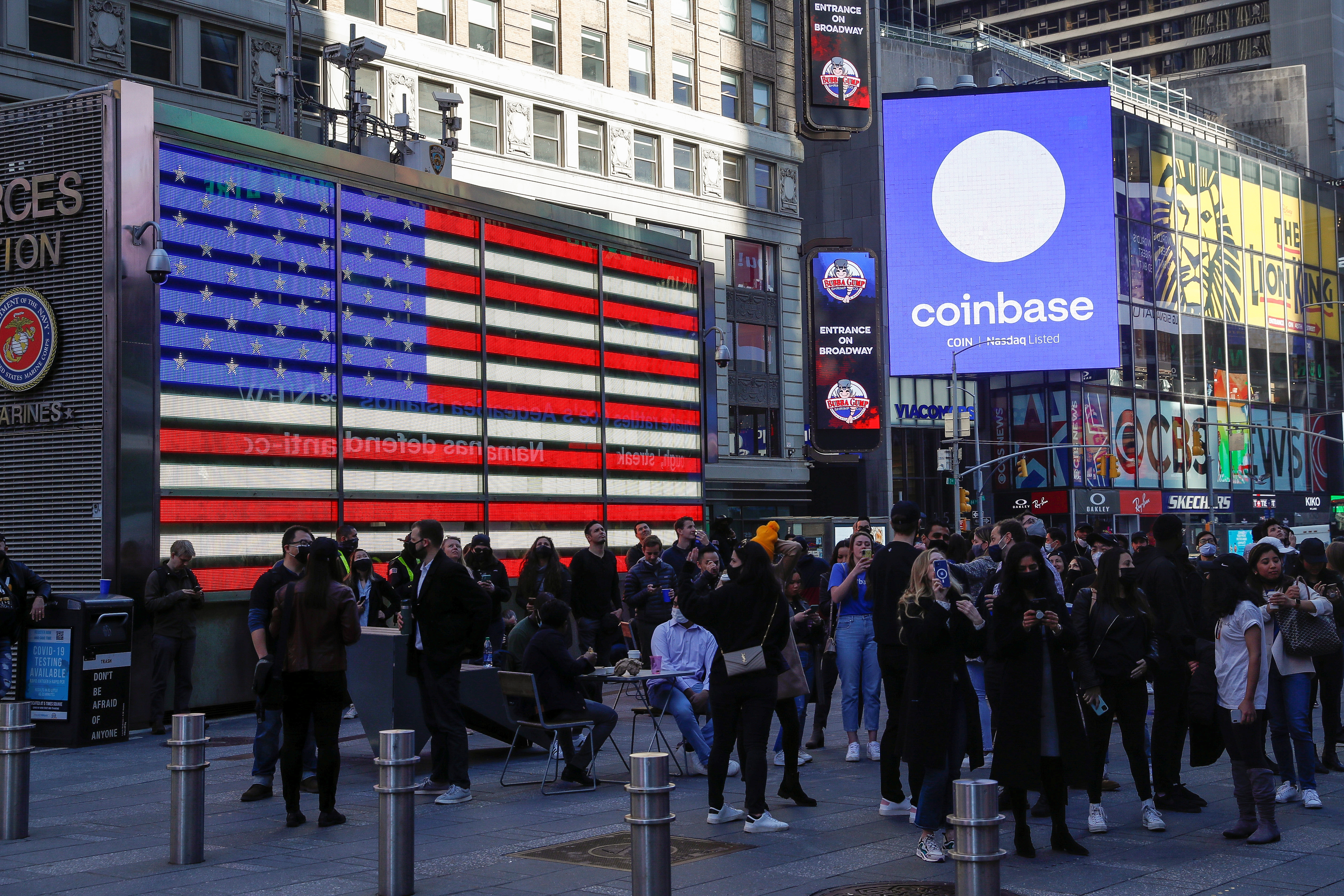 Employees of Coinbase Global Inc, the biggest U.S. cryptocurrency exchange, watch as their listing is displayed on the Nasdaq MarketSite jumbotron at Times Square in New York, U.S., April 14, 2021. REUTERS/Shannon Stapleton