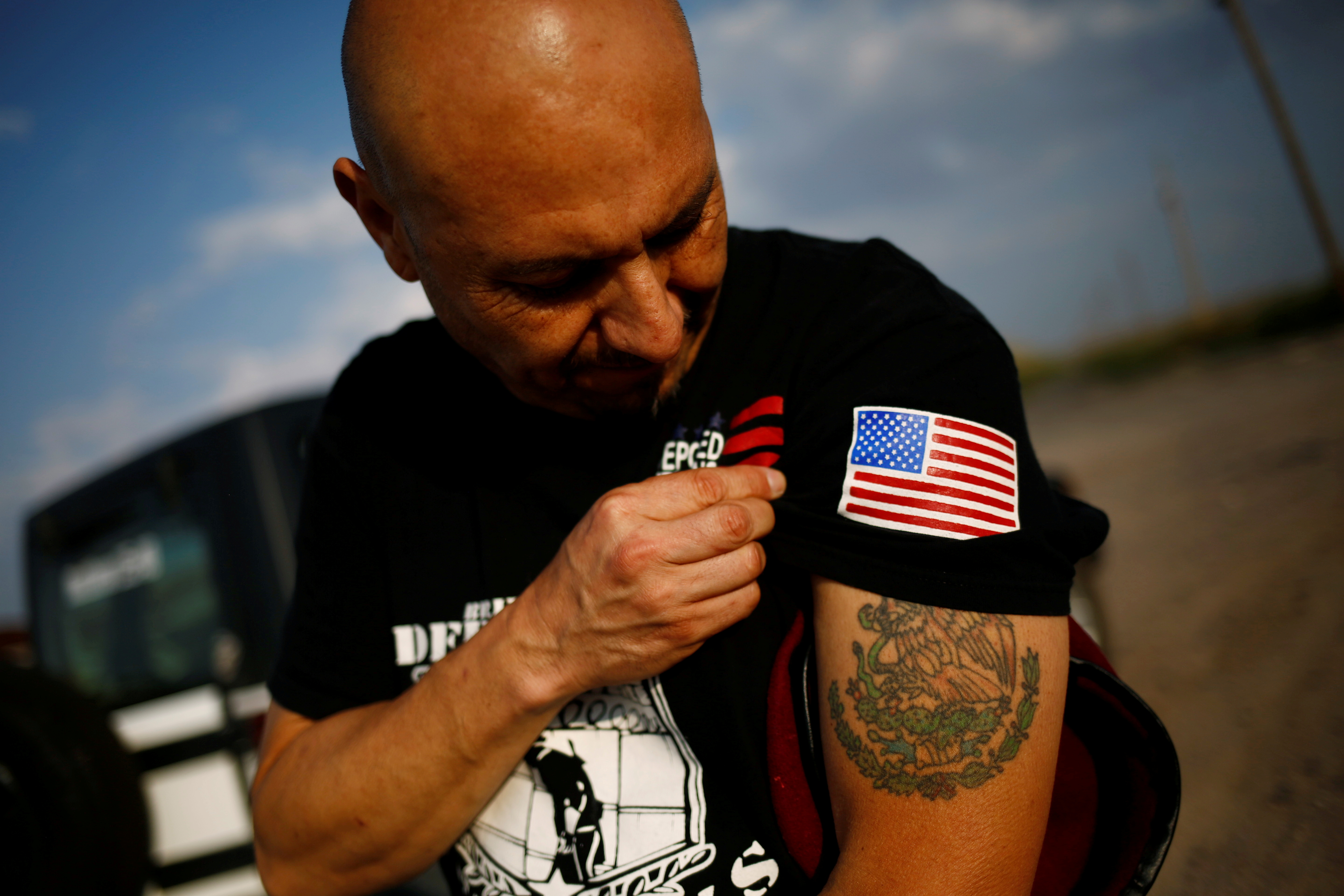 Hector Barajas, a veteran soldier of Mexican origin who said he served in the U.S Army but ended up being deported and after 14 years was allowed to return, displays the shield of the Mexican flag while takes part in the