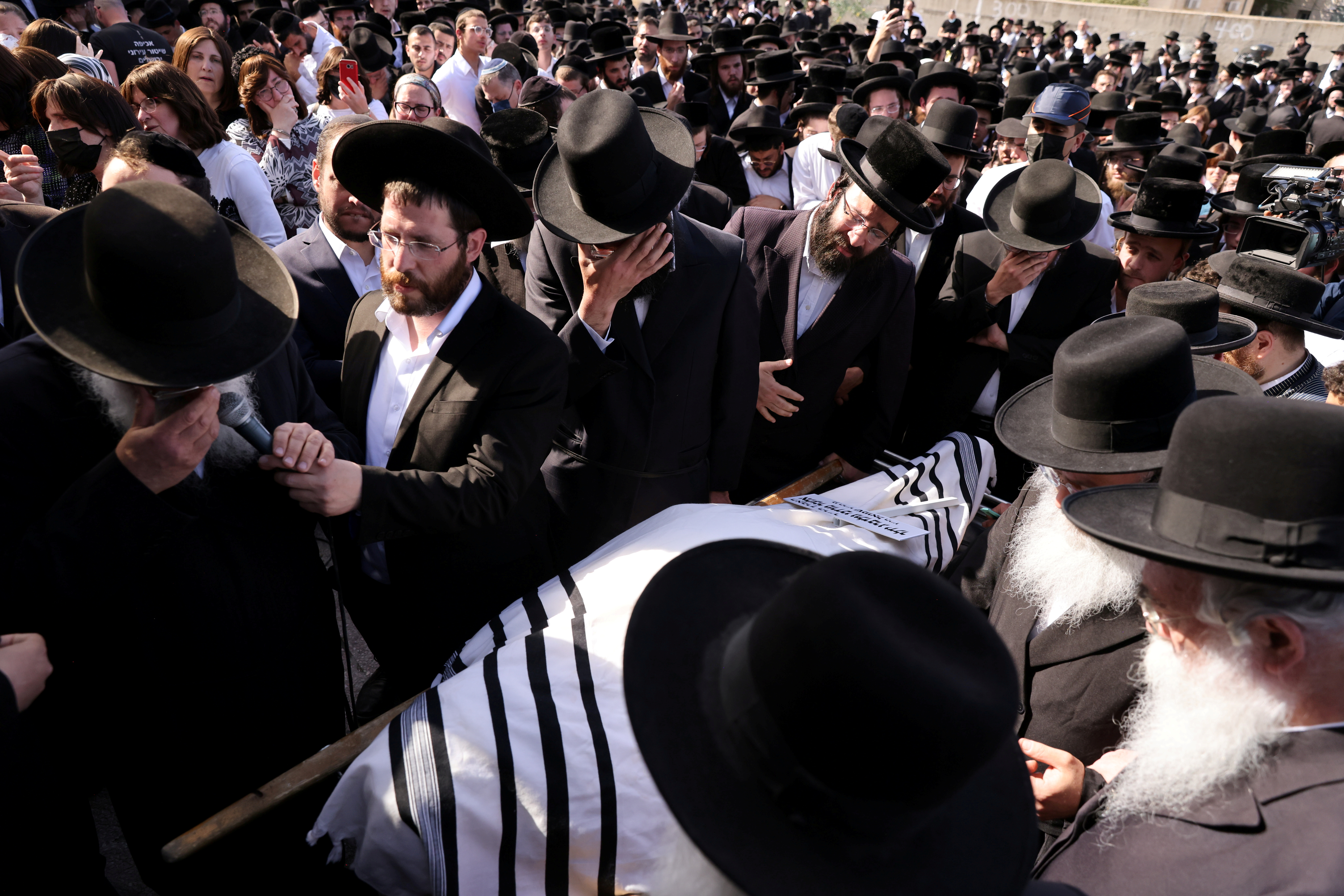 Ultra-Orthodox Jewish men react as they take part in a funeral for Rabbi Elazar Goldberg after he died during Lag B'Omer commemorations, in Jerusalem April 30, 2021. REUTERS/Ronen Zvulun/File Photo