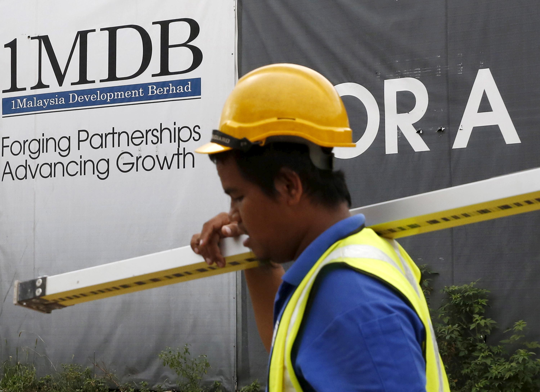 A construction worker walks past a 1Malaysia Development Berhad (1MDB) billboard at the Tun Razak Exchange development in Kuala Lumpur, Malaysia February 3, 2016. REUTERS/Olivia Harris