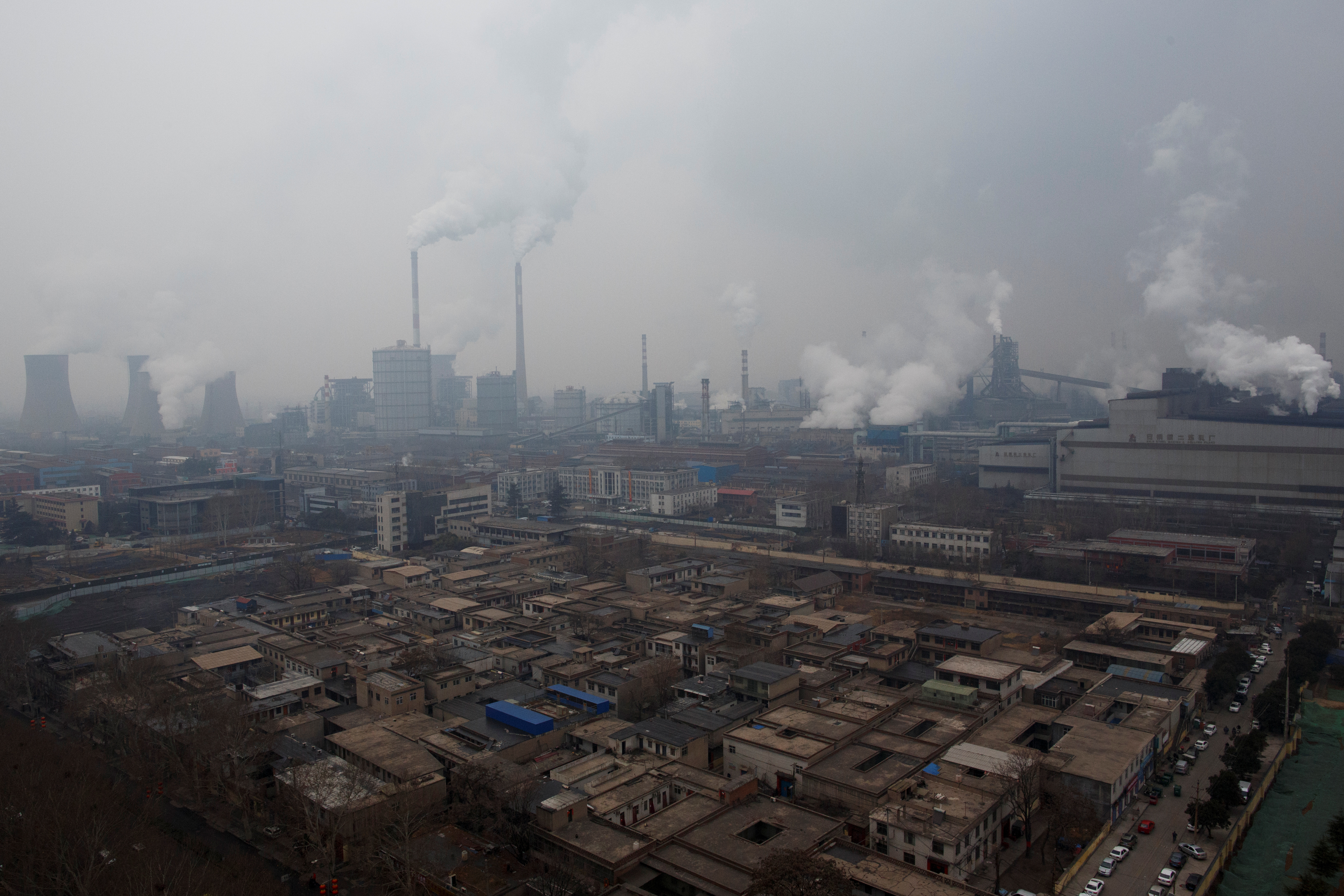Smoke stacks and cooling towers of a power plant rise above a low-rise neighborhood that borders a steel plant in Anyang, Henan province, China February 18, 2019. REUTERS/Thomas Peter