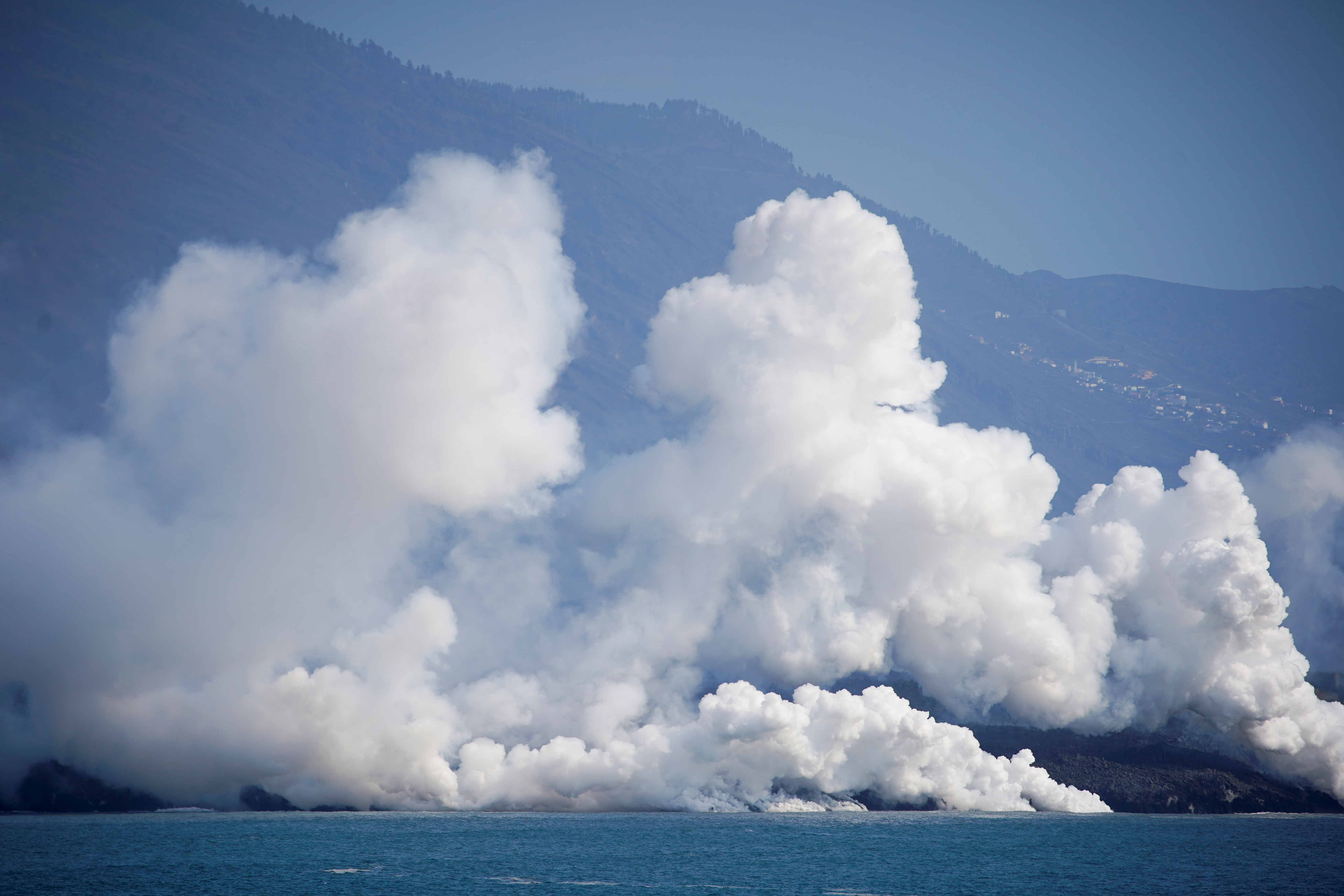 Smoke rises as lava flows into the sea following the eruption of a volcano, as seen from Tazacorte port, Canary Island of La Palma, Spain, October 6, 2021. REUTERS/Juan Medina