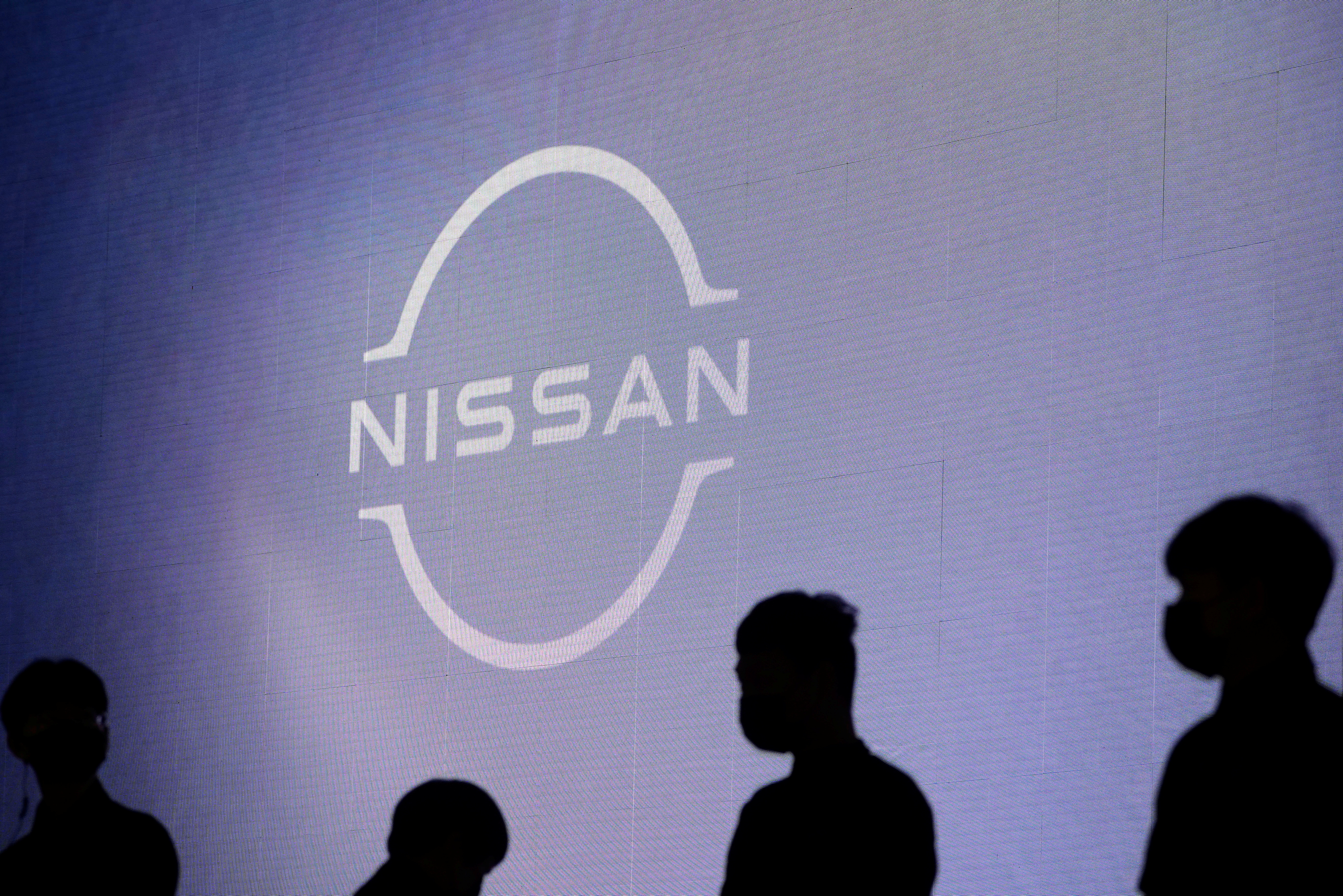 People stand near the Nissan logo during a media day for the Auto Shanghai show in Shanghai, China April 20, 2021. REUTERS/Aly Song