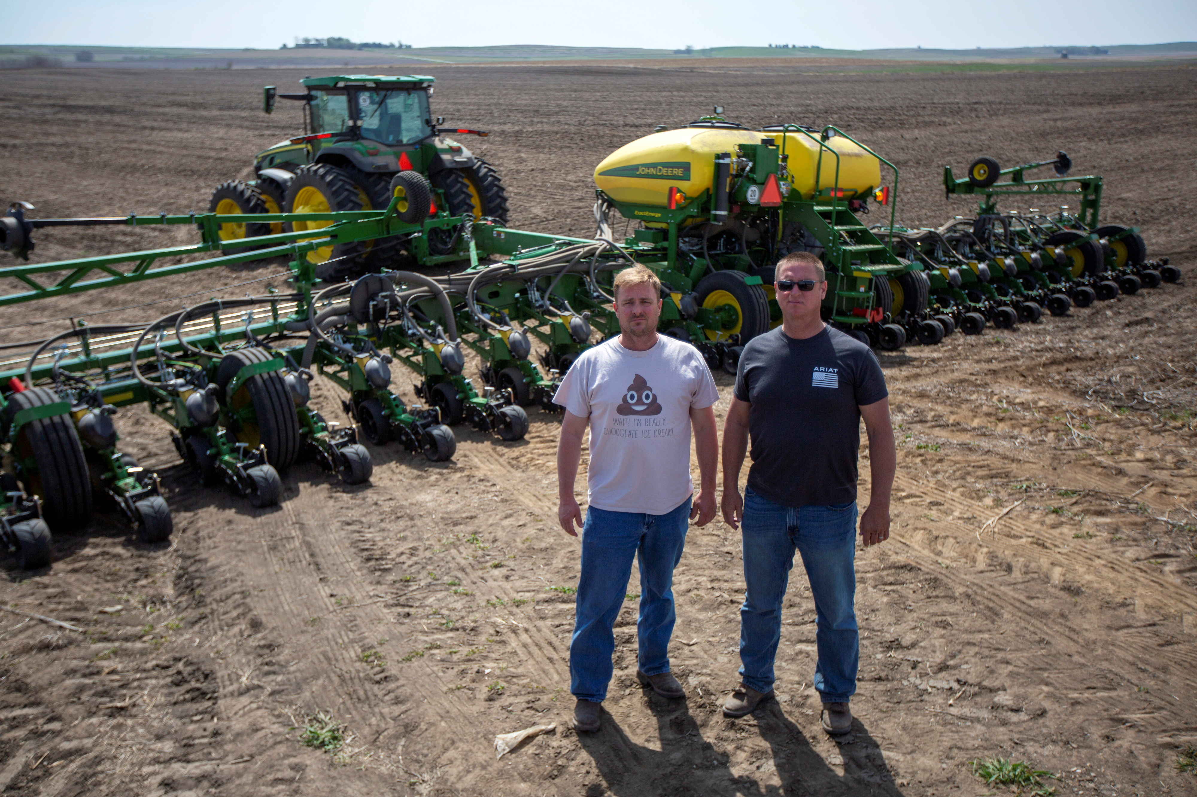 Brothers Chris and Bret Hays with their new tractor and planter in a field at their farm in Malvern, Iowa, U.S., April 27, 2021. REUTERS/Rachel Mummey