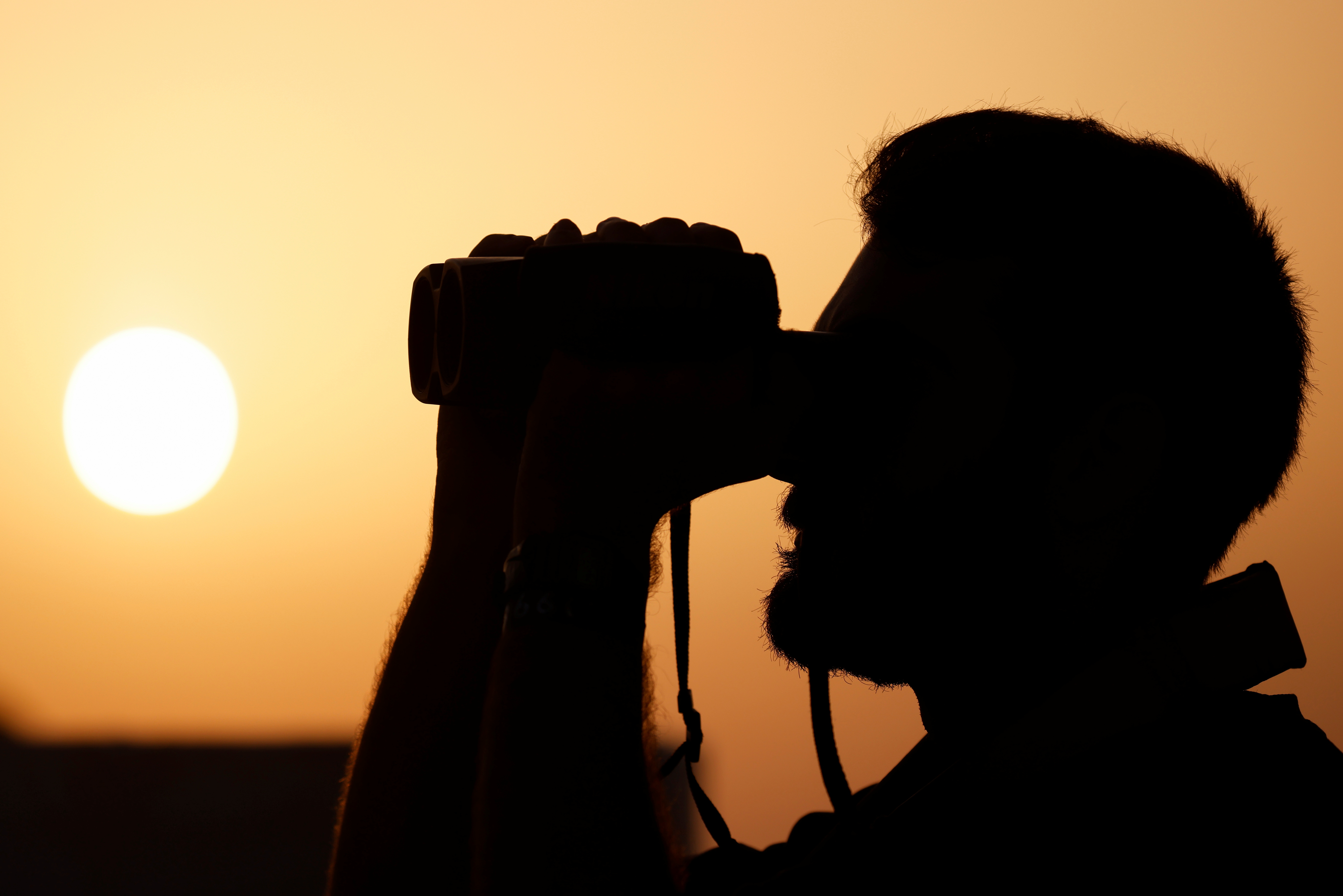 A crew member of the German NGO migrant rescue ship Sea-Watch 3 uses binoculars to keep watch for migrant boats at sunset in the search and rescue zone in international waters off the coast of Libya, in the western Mediterranean Sea, July 26, 2021.  REUTERS/Darrin Zammit Lupi