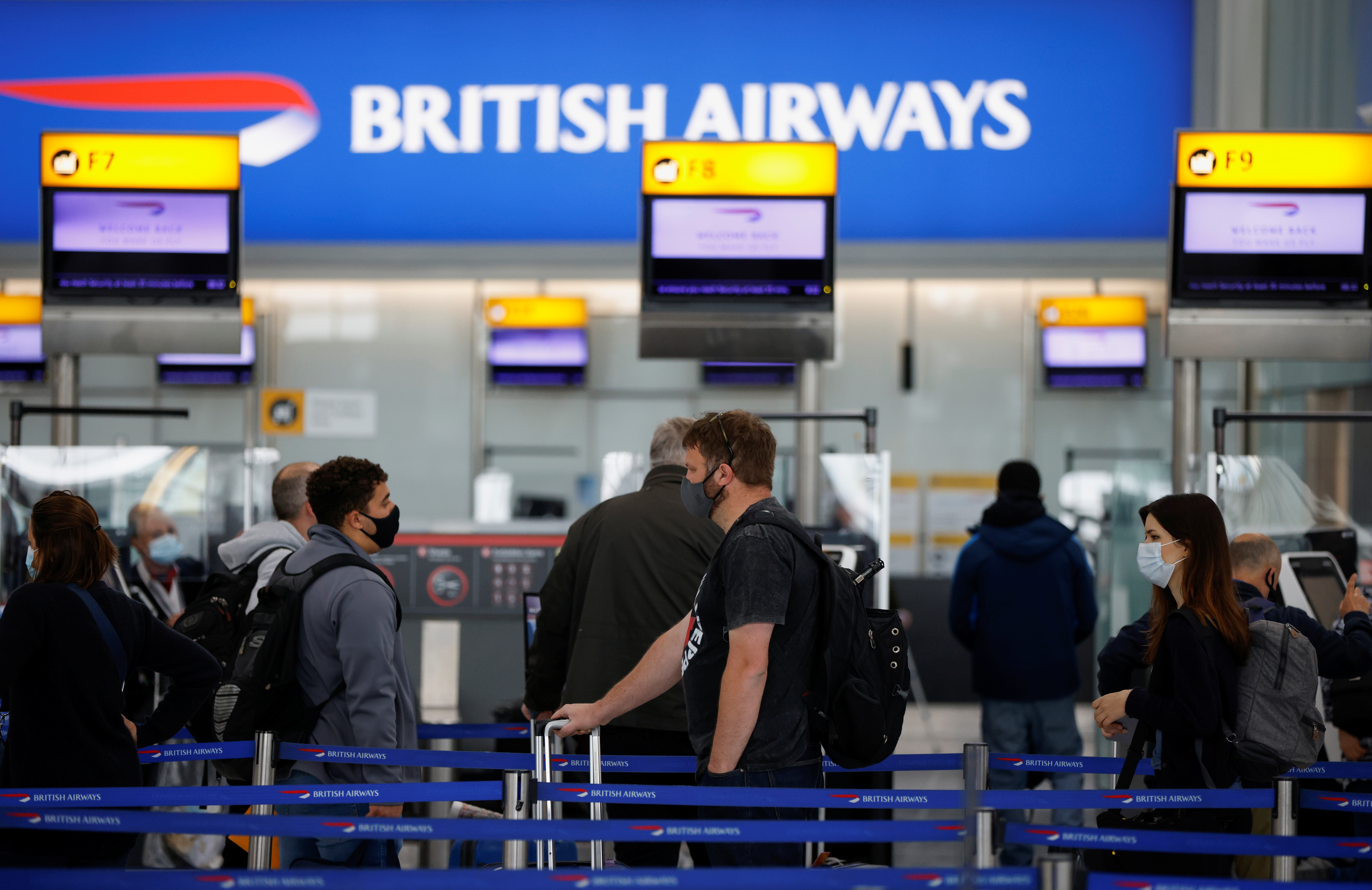 Passengers stand in a queue to the British Airways check-in desks in the departures area of Terminal 5 at Heathrow Airport in London, Britain, May 17, 2021. REUTERS/John Sibley/File photo
