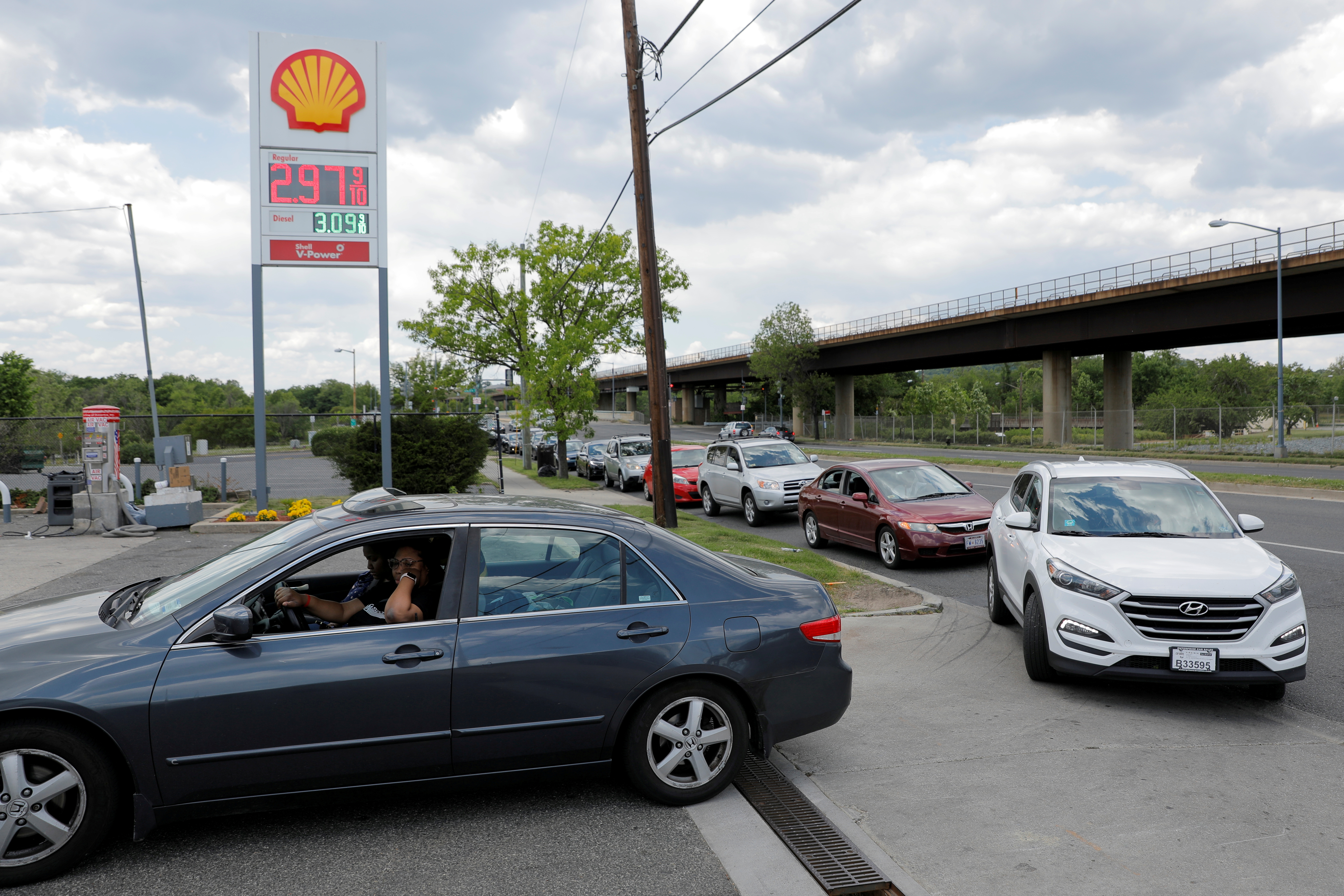 Cars queue as they wait to fill with gas at a Shell gas station, after a cyberattack crippled the biggest fuel pipeline in the country, run by Colonial Pipeline, in Washington, D.C., U.S., May 15, 2021. REUTERS/Andrew Kelly/File Photo