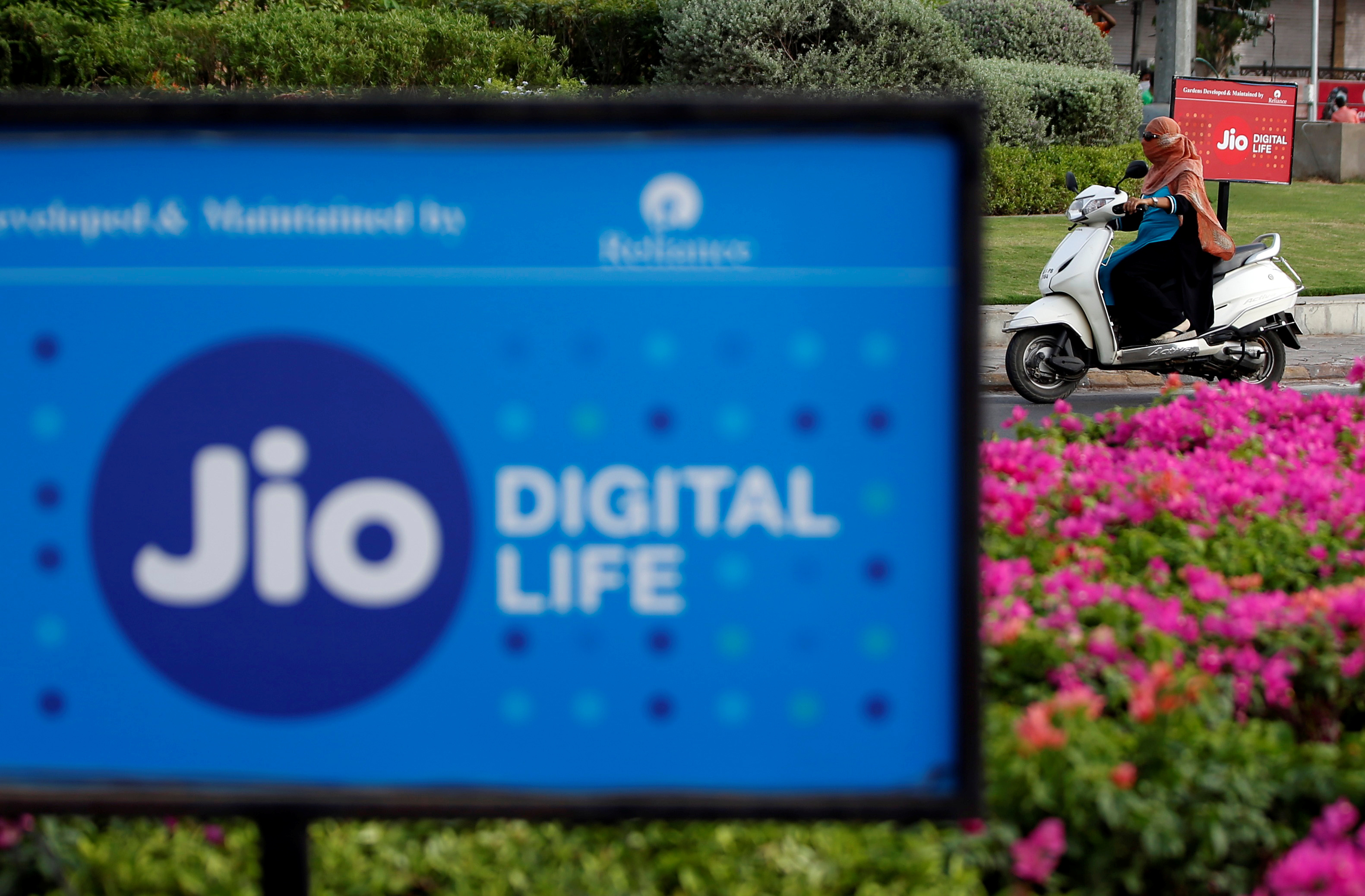 A woman rides her scooter past advertisements of Reliance Industries' Jio telecoms unit, in Ahmedabad, India, July 5, 2018. REUTERS/Amit Dave
