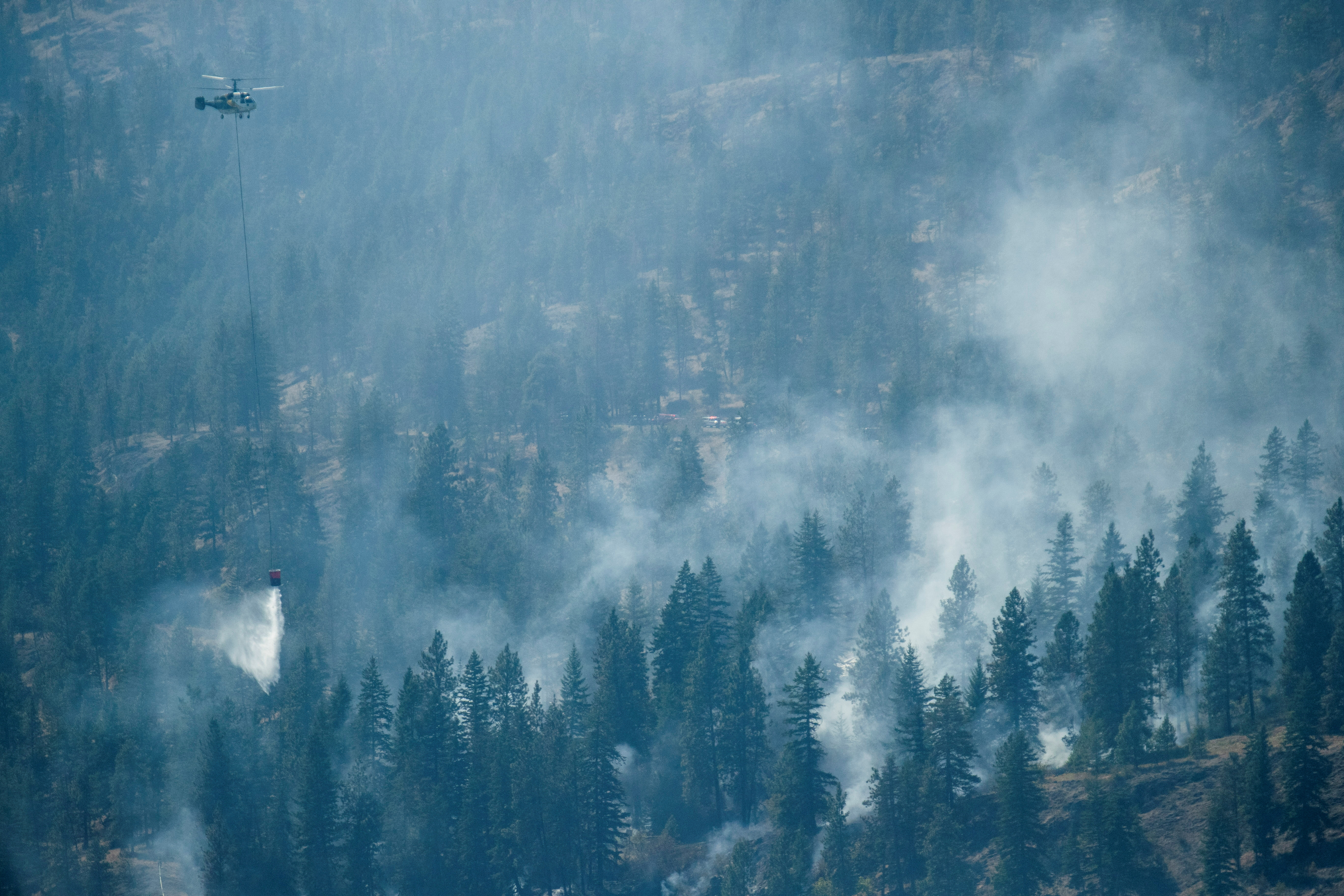 A helicopter battles the Bear Creek fire that sprung up south of the White Rock forest on Westside Rd. near Fintry, Canada, August 24, 2021. REUTERS/Artur Gajda