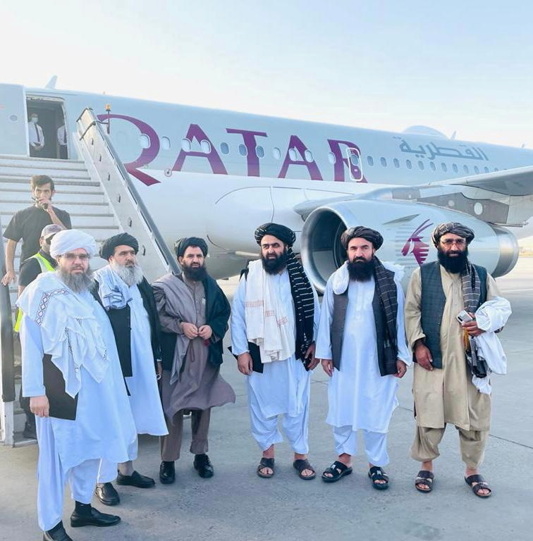 Taliban delegates stand in front of a Qatar Airways plane in an unidentified location in Afghanistan, in this handout photo uploaded to social media on October 8, 2021. Picture uploaded on on October 8, 2021. Social media handout/via REUTERS