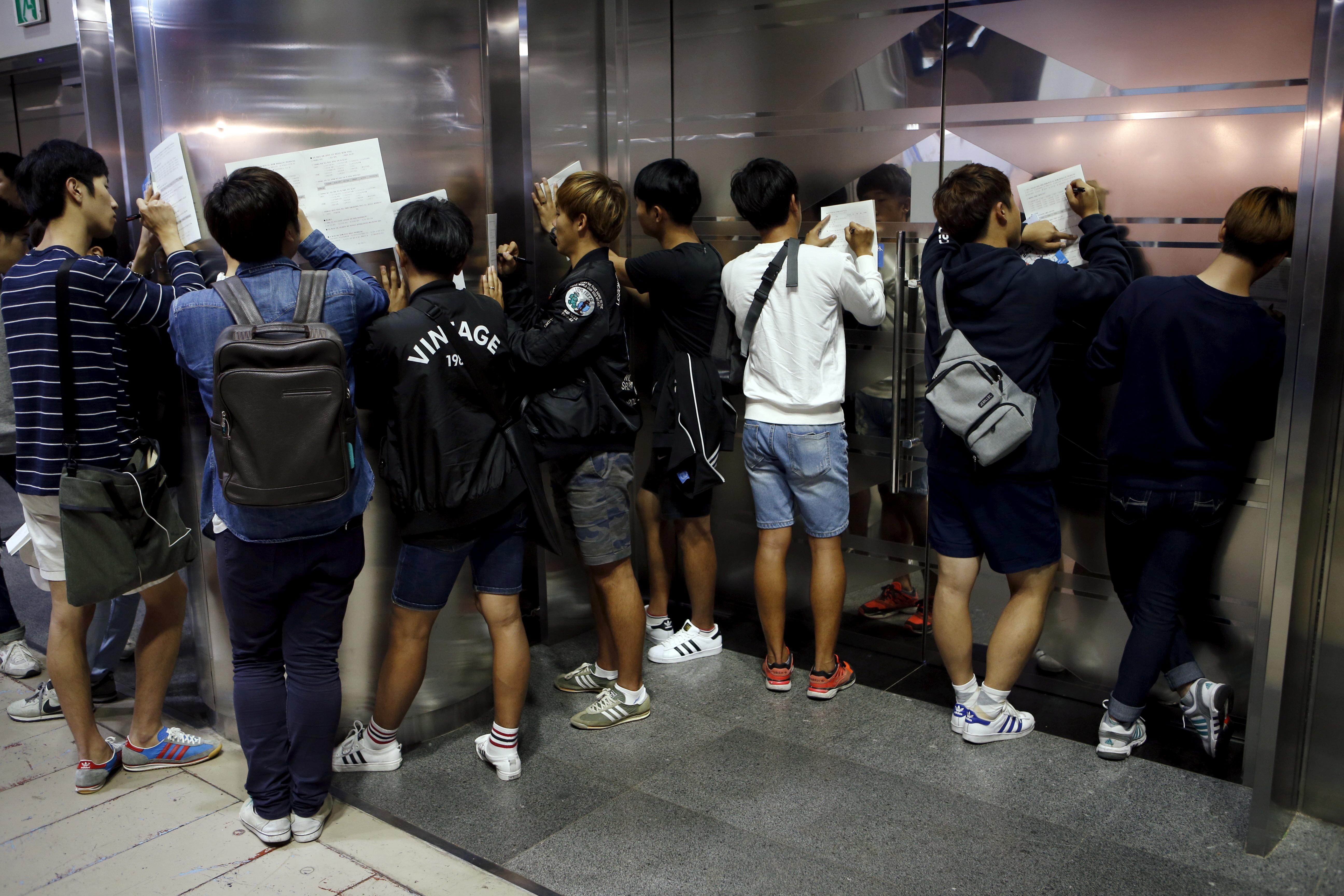 University students write on documents at an employment fair in Seoul, South Korea, September 23, 2015. REUTERS/Kim Hong-Ji/File Photo