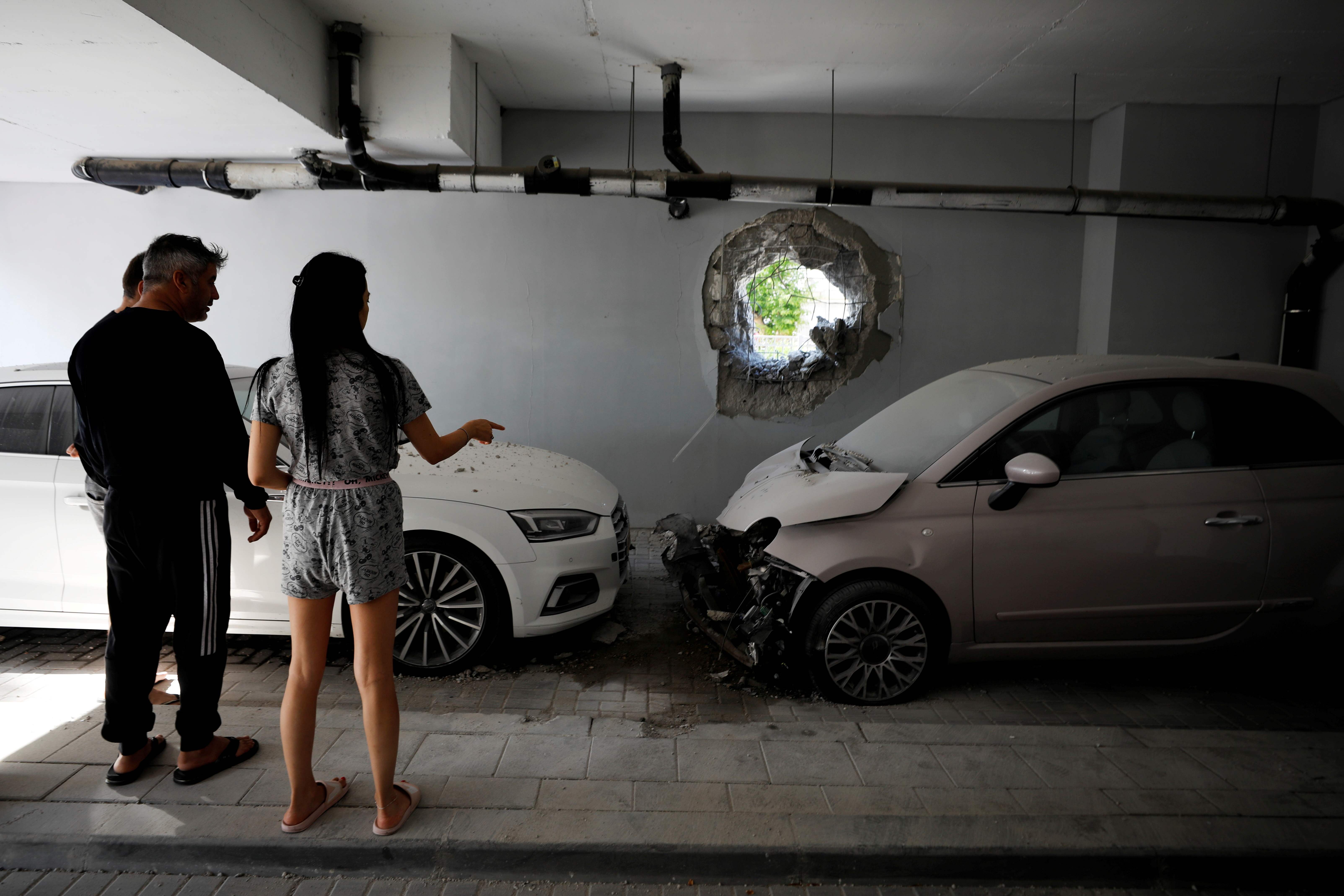 Residents look at their cars at the parking area under a residential building in Ashkelon, Israel, which was damaged by a direct hit from a rocket launched overnight from the Gaza Strip May 14, 2021. REUTERS/Amir Cohen