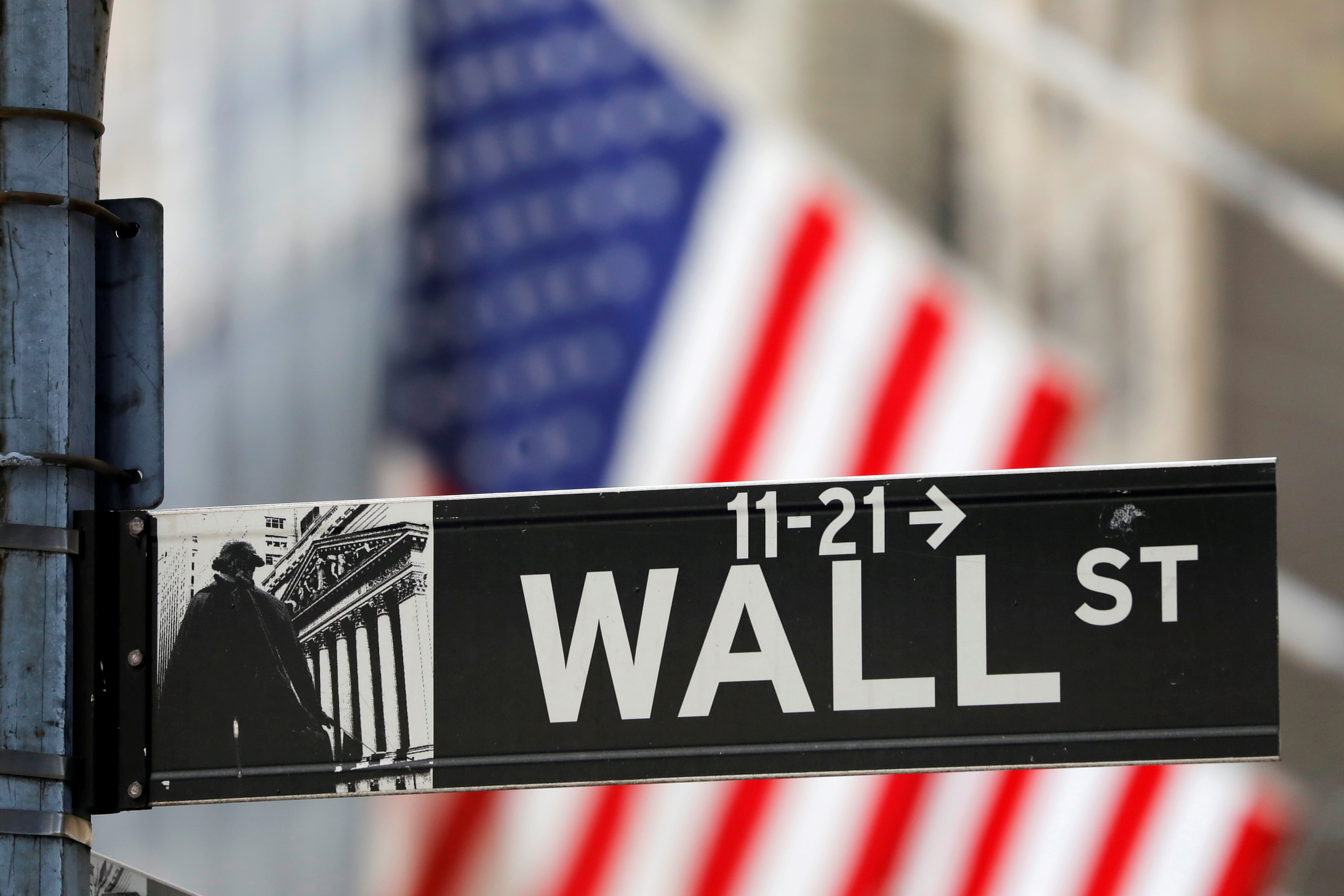 A street sign for Wall Street is seen outside the New York Stock Exchange (NYSE) in New York City, New York, U.S., July 19, 2021. REUTERS/Andrew Kelly/File Photo