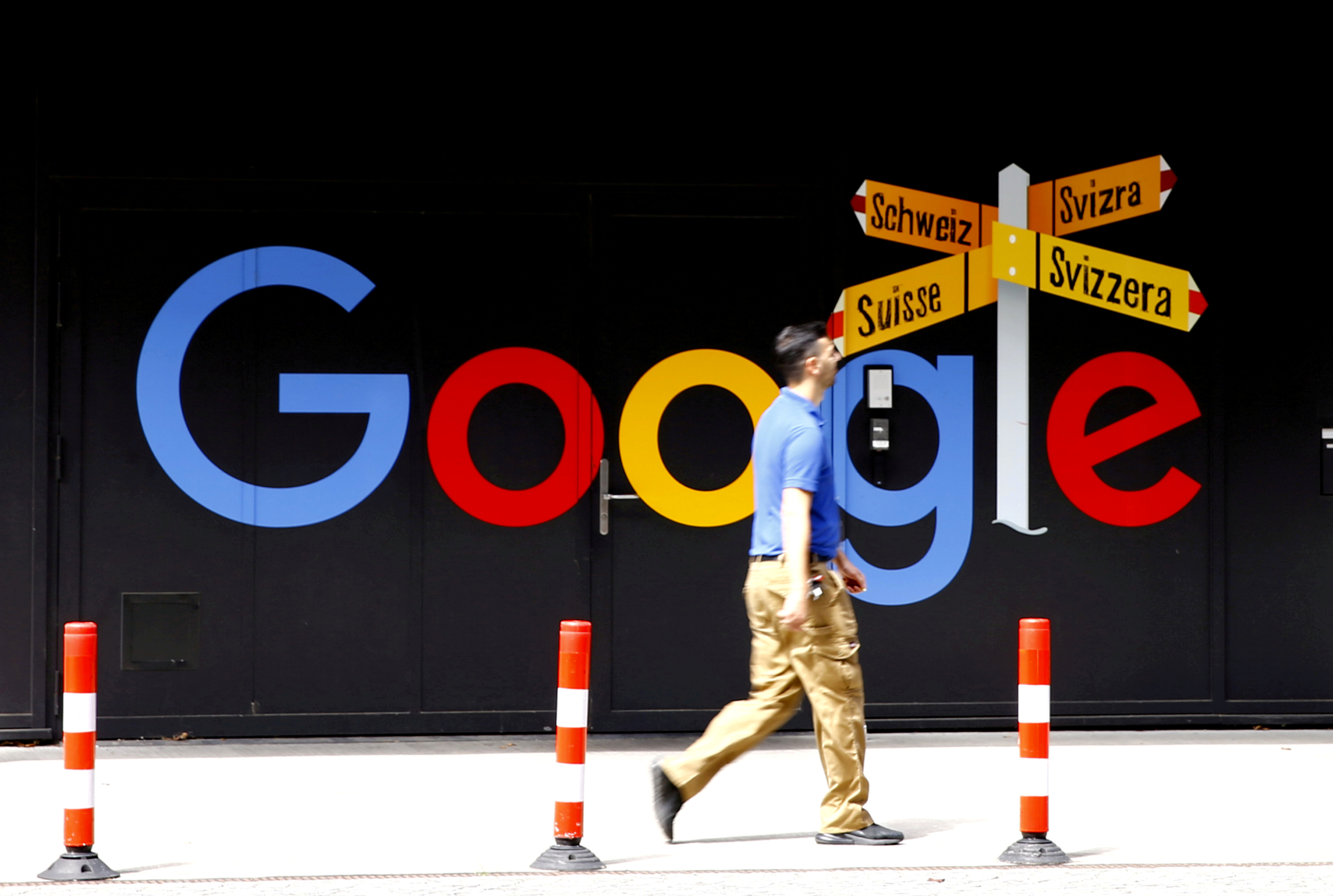 A man walks past a logo of Google in front of at an office building in Zurich, Switzerland July 1, 2020.   REUTERS/Arnd Wiegmann/File Photo