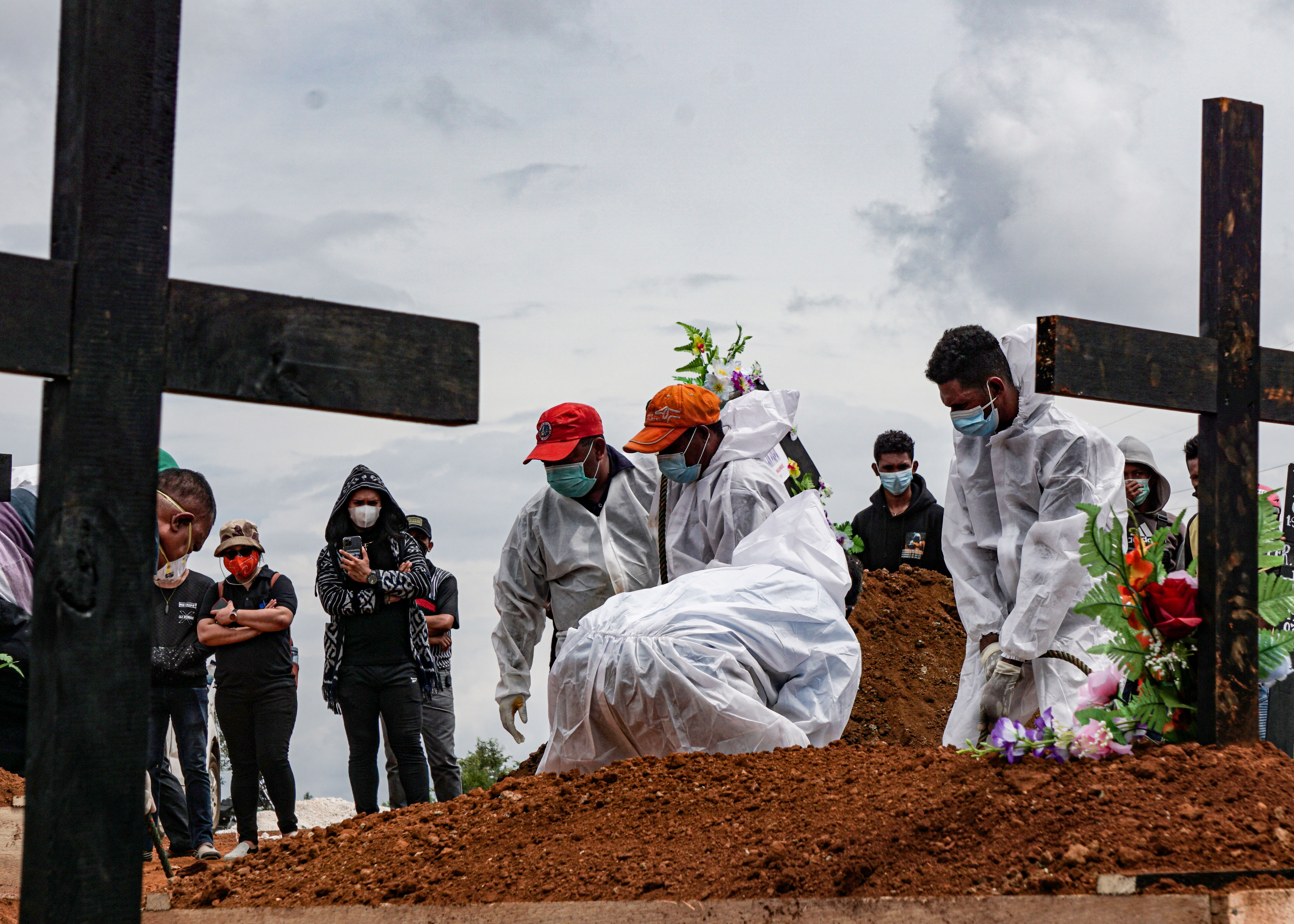 Gravediggers wearing personal protective equipment (PPE) burry a coffin at a burial area provided by the government for coronavirus disease (COVID-19) victims, as cases surge in Jayapura, Papua, Indonesia July 20, 2021, in this photo taken by Antara Foto/Indrayadi TH/via REUTERS