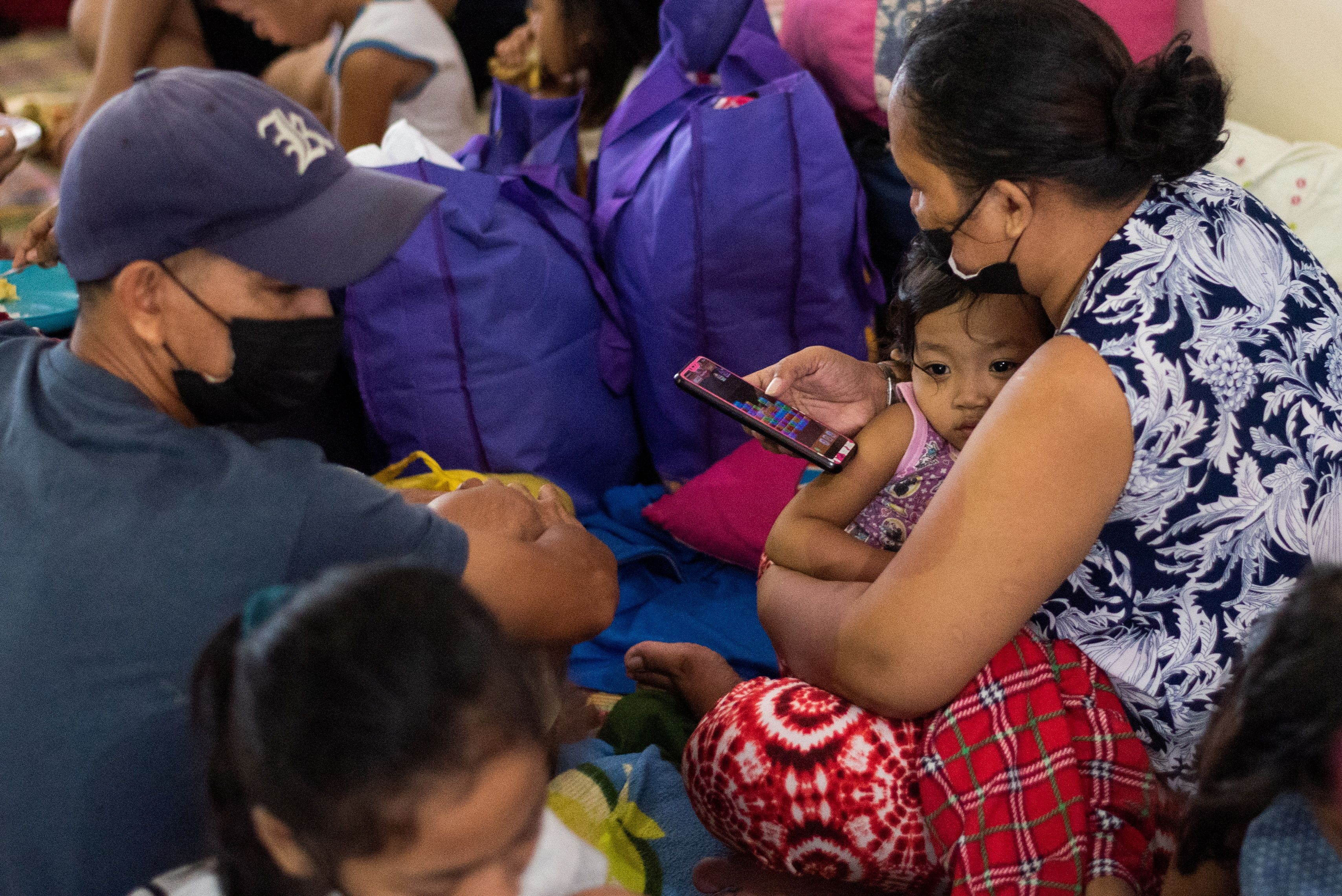 A child leans on her mother after being evacuated at a school following heavy rains that caused flooding in some areas in Marikina city, Metro Manila, Philippines, July 24, 2021. REUTERS/Lisa Marie David