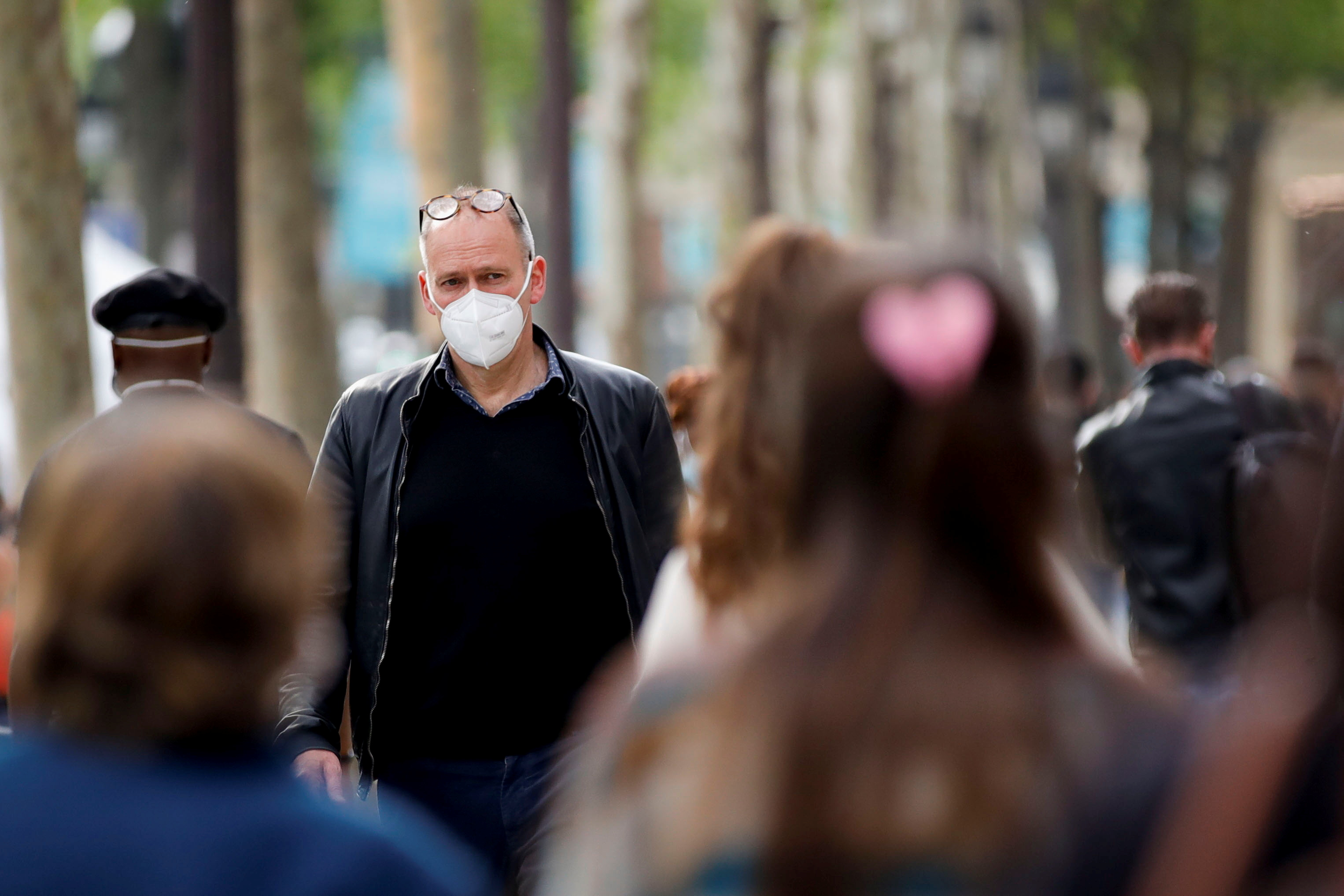 People wearing protective face masks walk on the Champs Elysees Avenue, amid the coronavirus disease (COVID-19) outbreak, in France, May 27, 2021. REUTERS/Sarah Meyssonnier