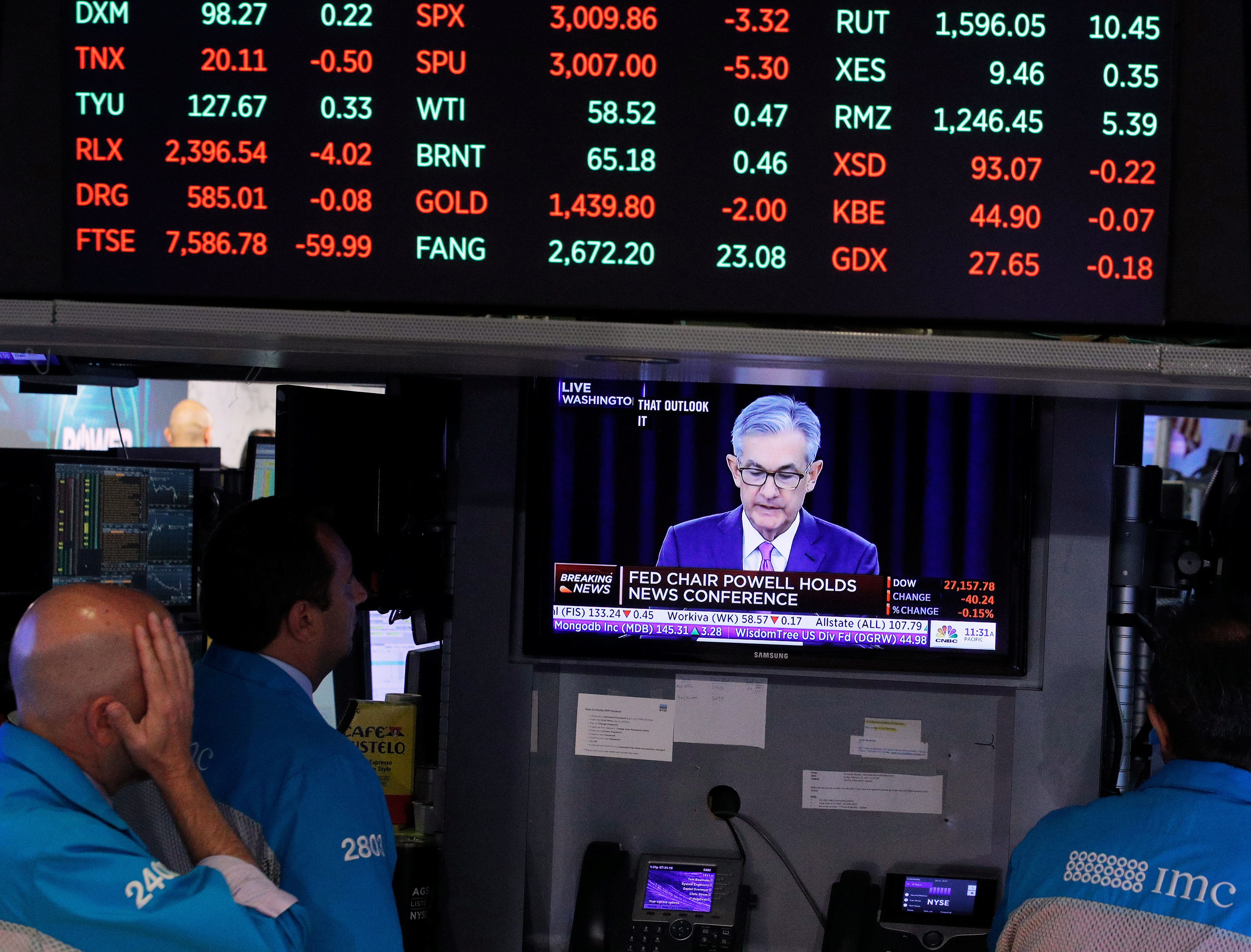 Traders look on as a screen shows Federal Reserve Chairman Jerome Powell's news conference after the U.S. Federal Reserve interest rates announcement on the floor of the New York Stock Exchange (NYSE) in New York, U.S., July 31, 2019. REUTERS/Brendan McDermid/File Photo