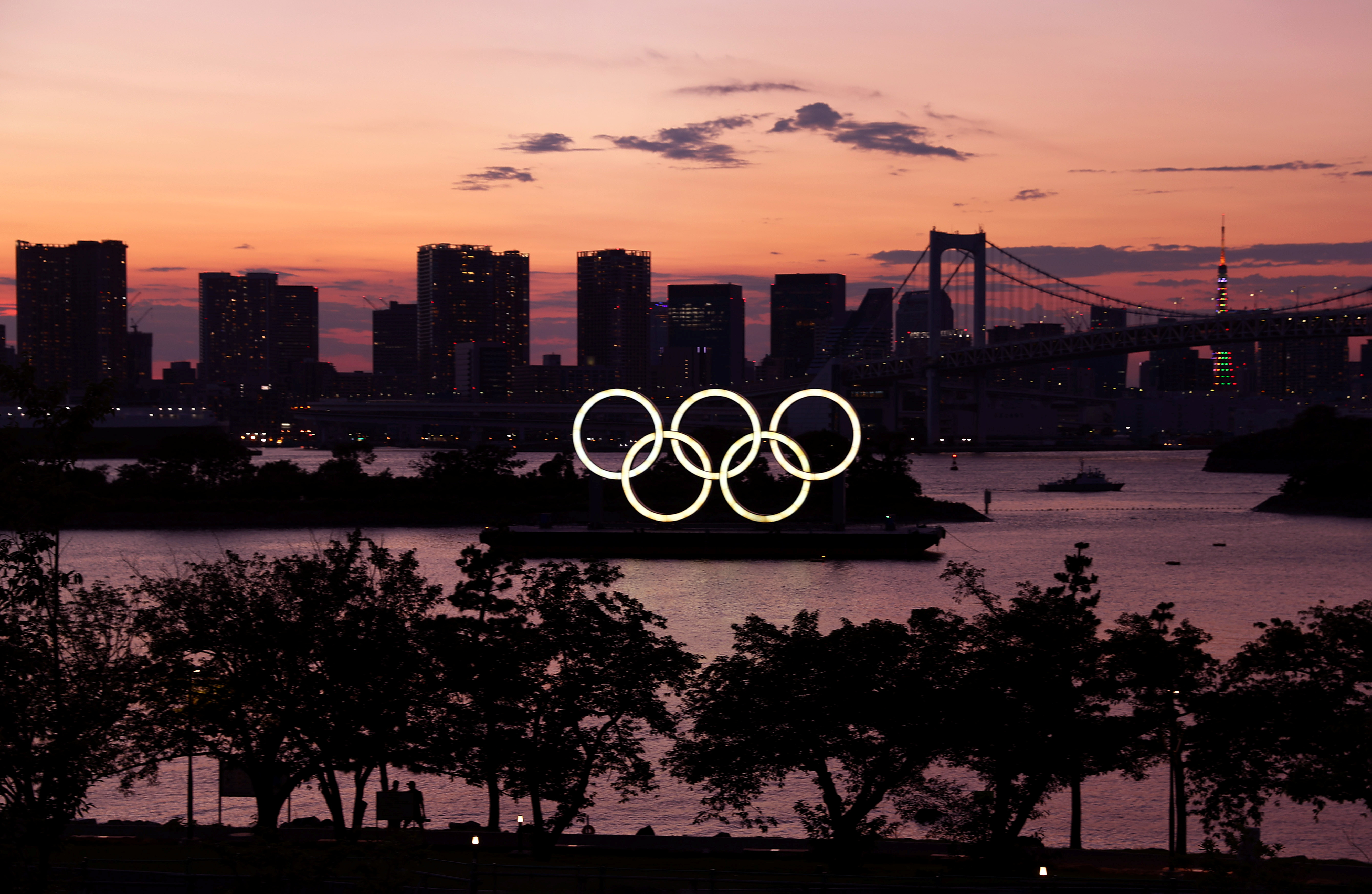 The Olympic Rings are seen in front of the skyline during sunset one night ahead of the official opening of the Tokyo 2020 Olympic Games in Tokyo, Japan, July 22, 2021.   REUTERS/Kai Pfaffenbach