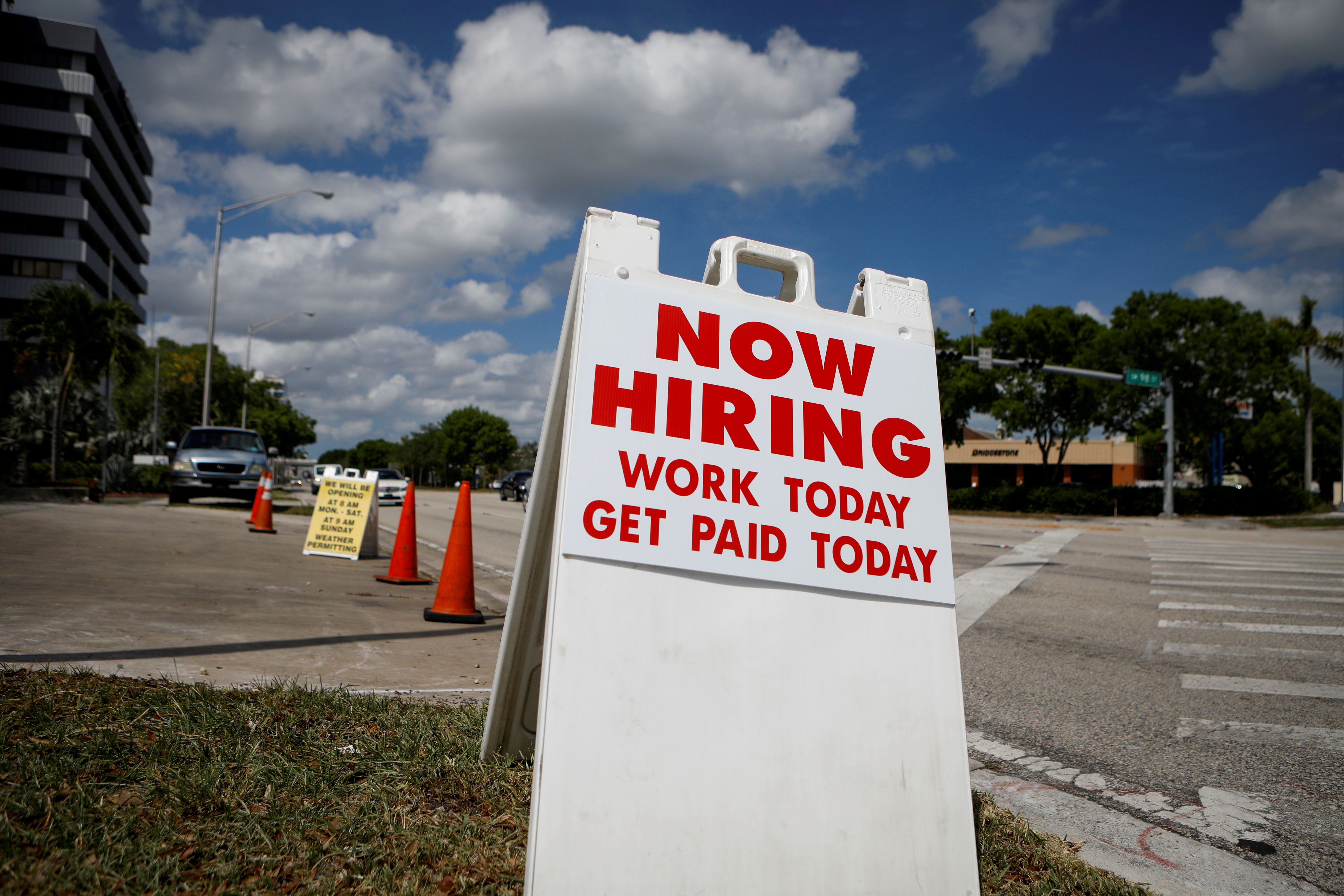 """A """"Now Hiring"""" sign advertising jobs at a hand car wash is seen along a street in Miami, Florida, U.S. May 8, 2020. REUTERS/Marco Bello/File Photo"""