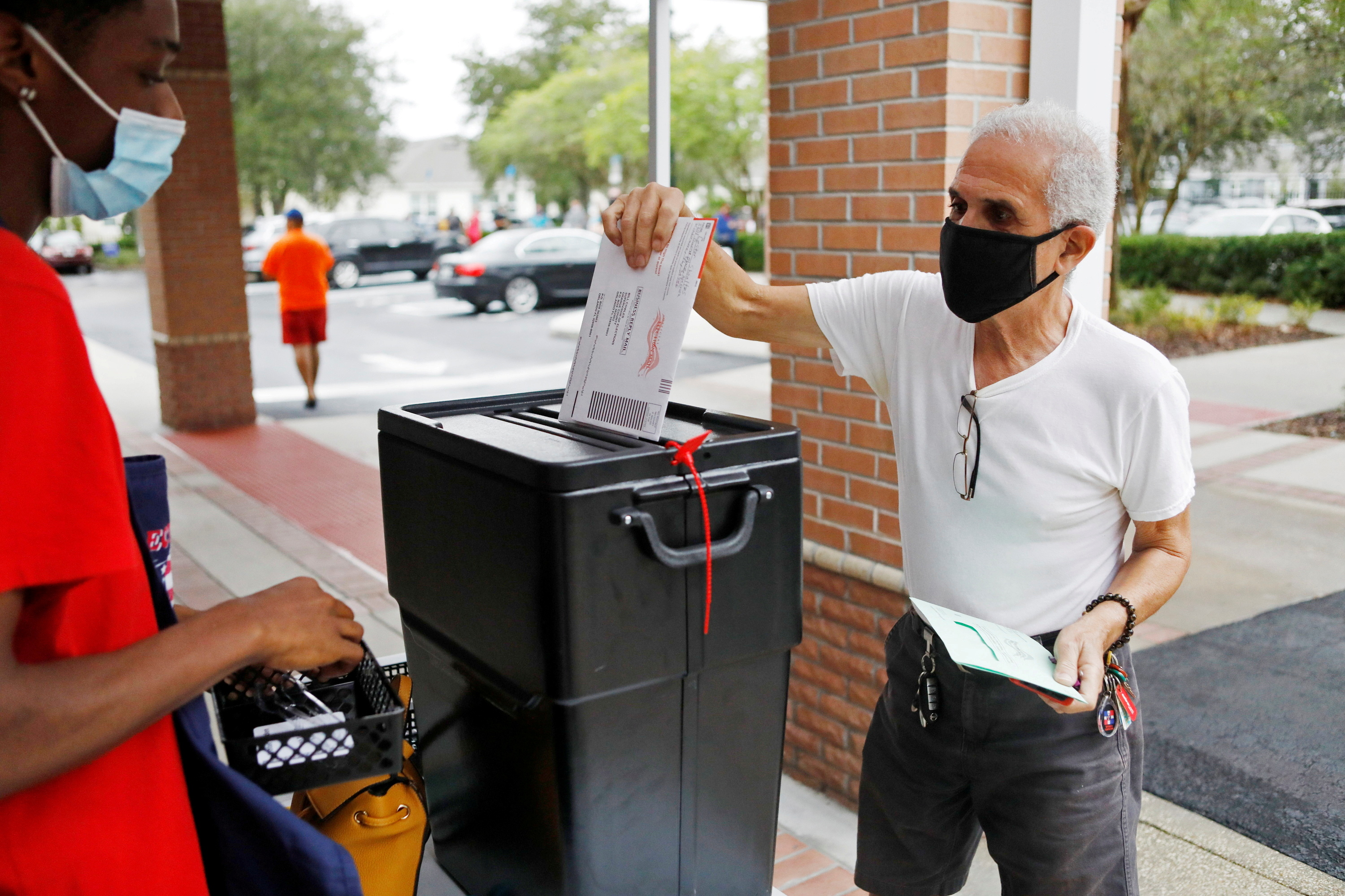 Florida resident Valentine Lugo casts his mail-in ballot at the Winter Garden Library polling station as early voting begins ahead of the election in Orlando, Florida, U.S. October 19, 2020.  REUTERS/Octavio Jones