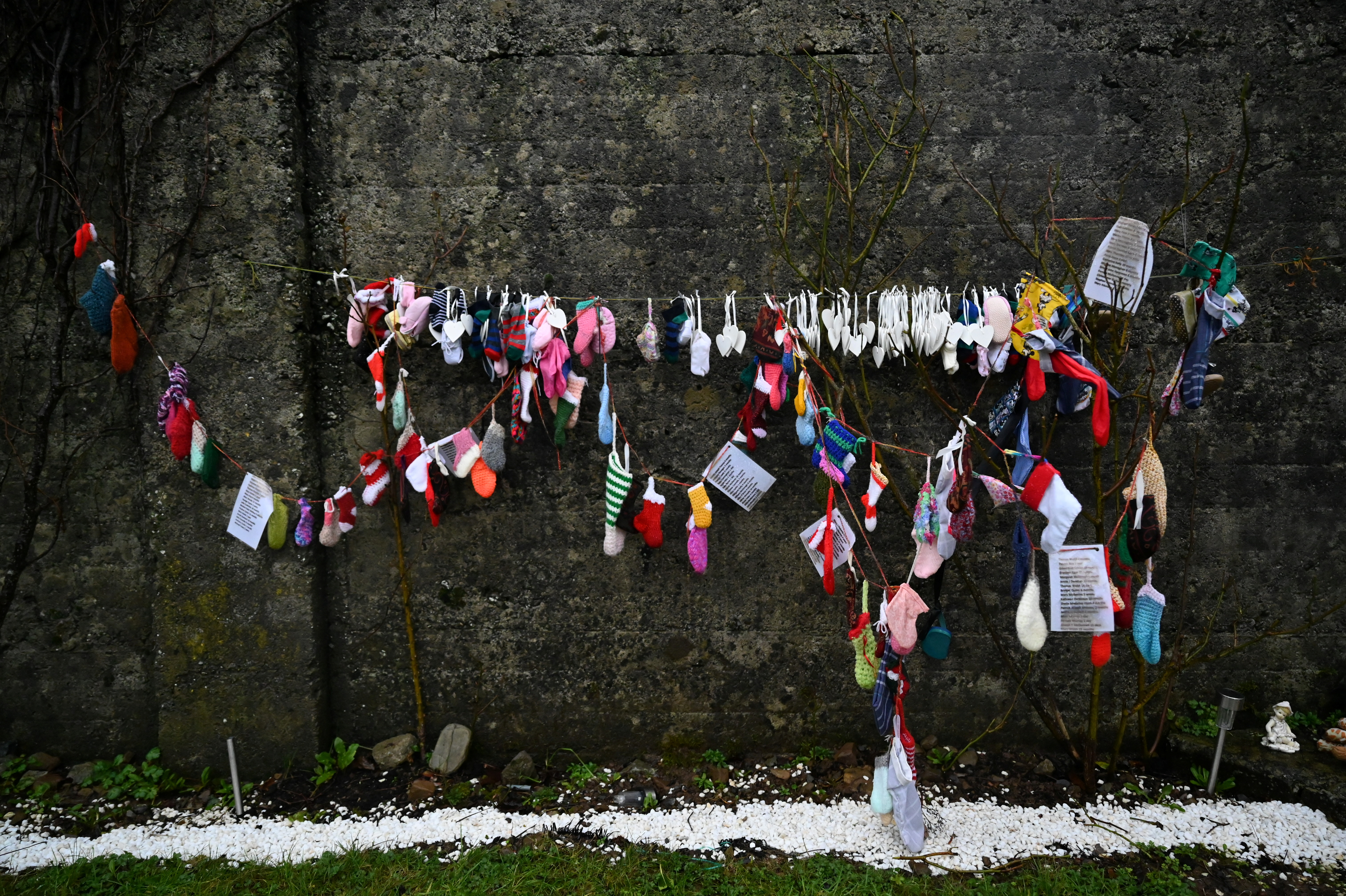 Children's socks and other items hang on a wall at the Tuam graveyard, where the bodies of 796 babies were uncovered at the site of a former Catholic home for unmarried mothers and their children on the day a government-ordered inquiry into former Church-run homes for unmarried mothers is formally published, in Tuam, Ireland, January 12, 2021. REUTERS/Clodagh Kilcoyne