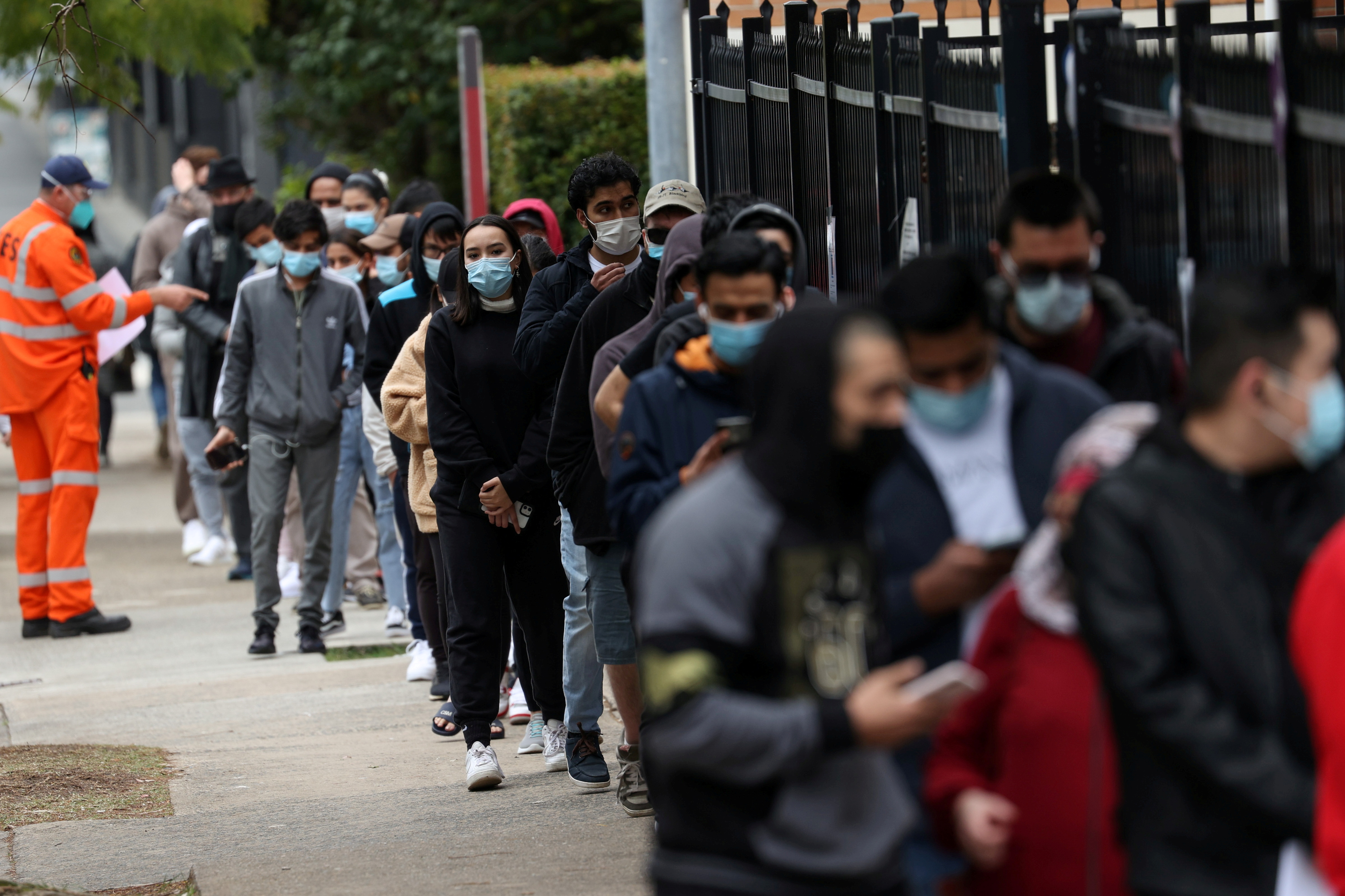 People wait in line outside a coronavirus disease (COVID-19) vaccination clinic in the Bankstown suburb during a lockdown to curb an outbreak of cases in Sydney, Australia, August 25, 2021.  REUTERS/Loren Elliott/File Photo