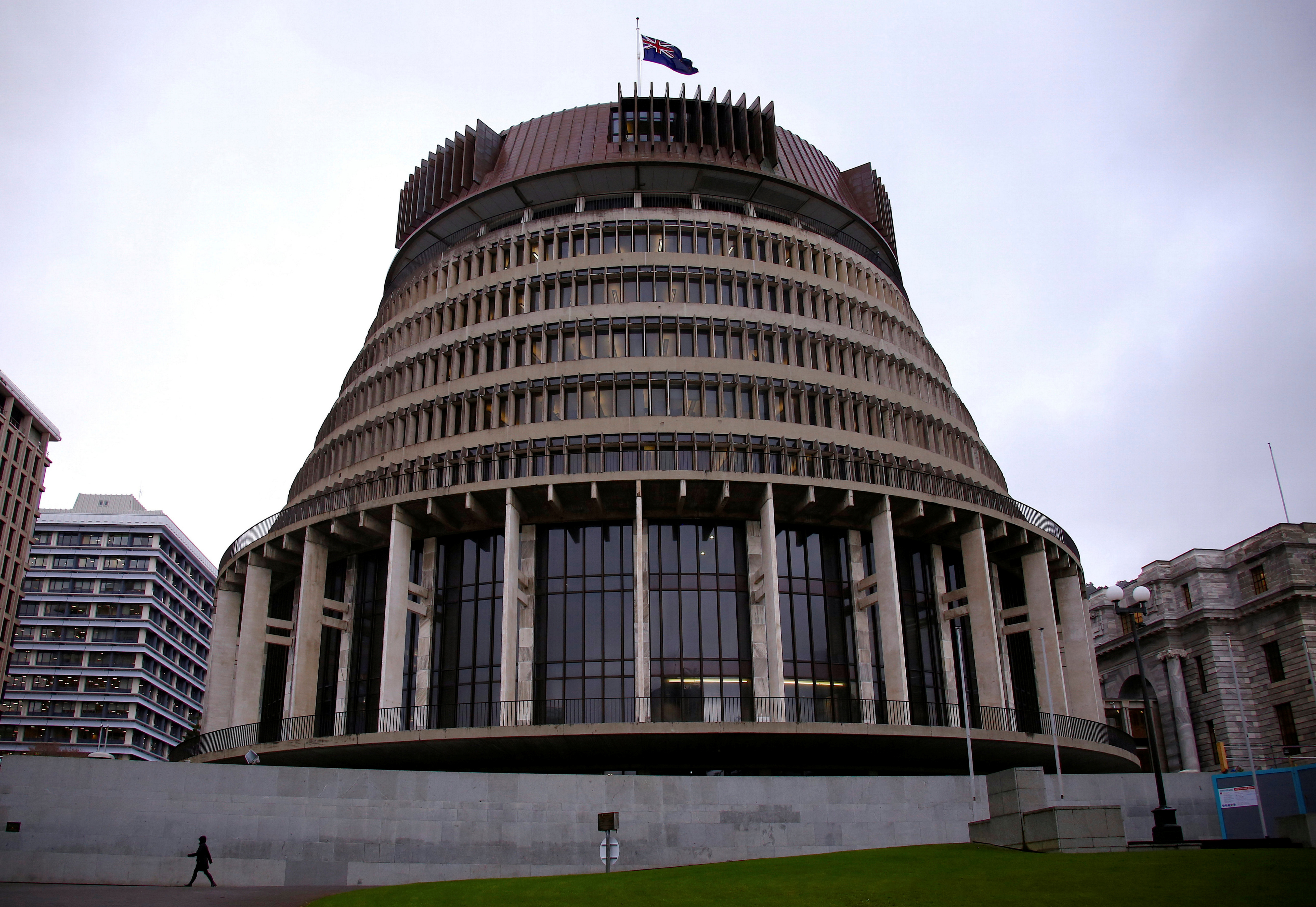 A pedestrian walks past the New Zealand parliament building known as the Beehive in central Wellington, New Zealand, July 3, 2017. Picture taken July 3, 2017.   REUTERS/David Gray