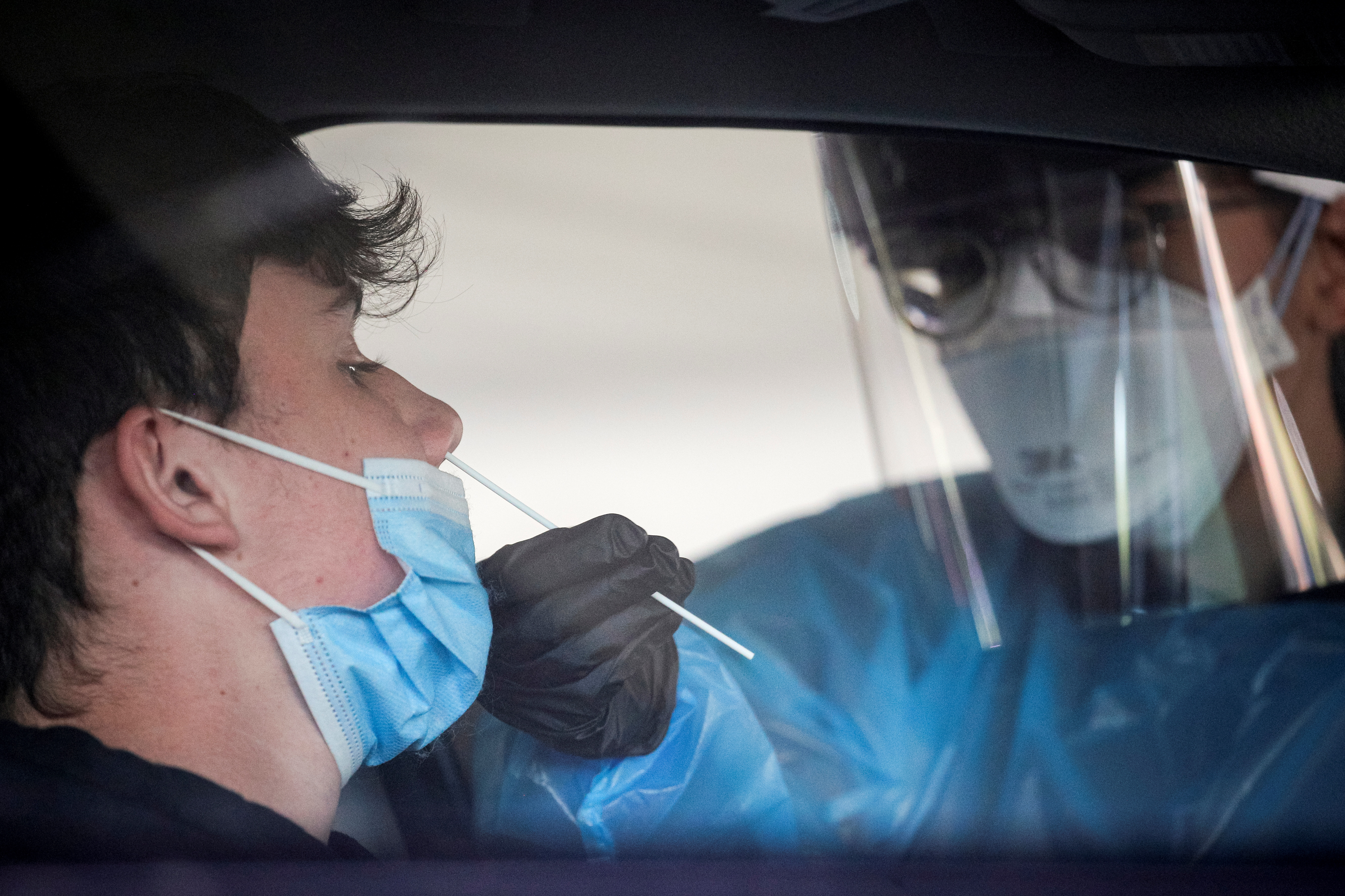 A health care worker gives a coronavirus test at a COVID drive-thru testing center at Bergen Community College, as the global outbreak of the coronavirus disease (COVID-19) continues, in Paramus, New Jersey, U.S., December 3, 2020.  REUTERS/Brendan McDermid