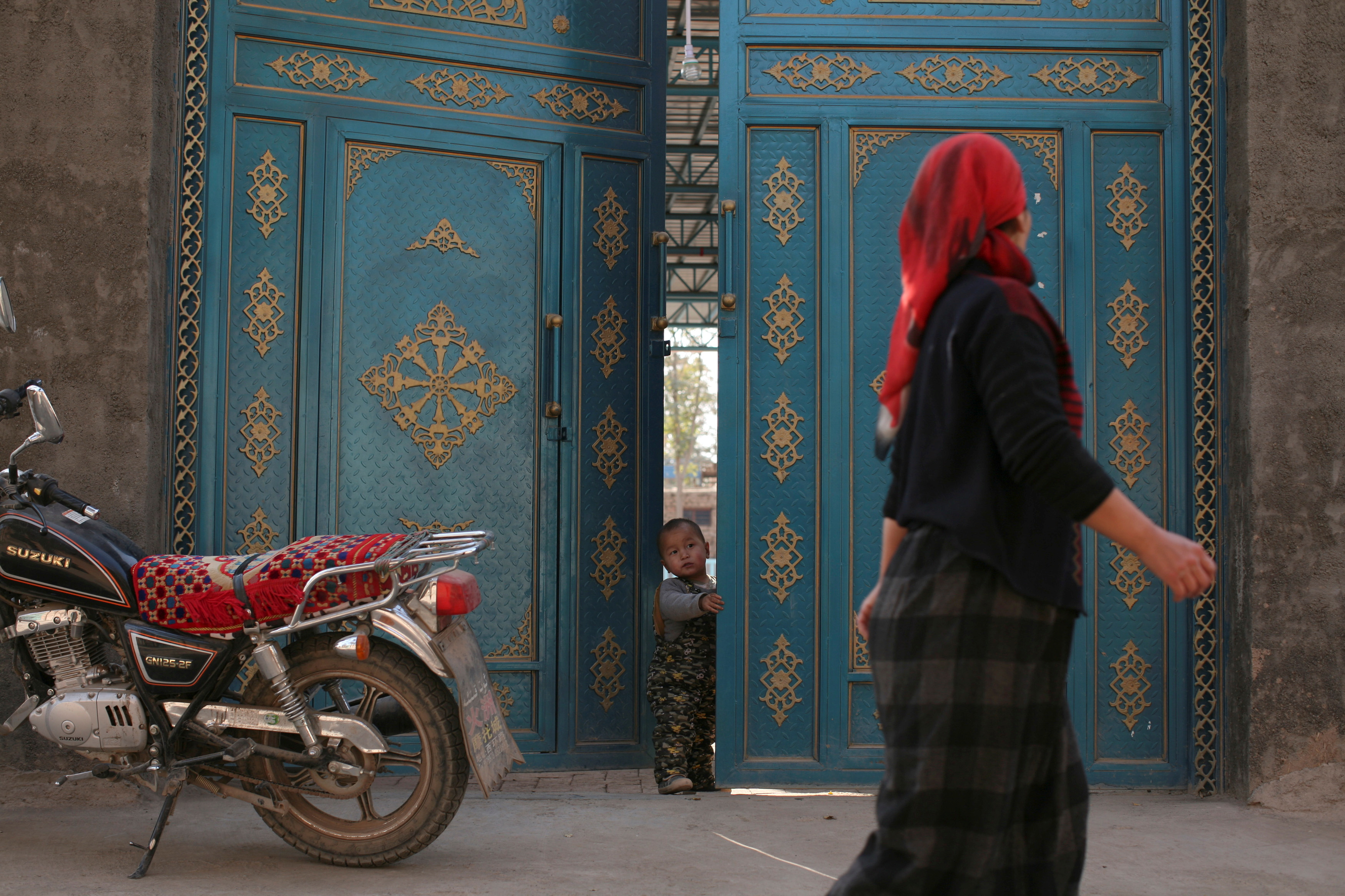 A child looks out from a door as a Uighur woman walks by in a residential area in Turpan, Xinjiang Uighur Autonomous Region October 31, 2013.  REUTERS/Michael Martina/File Photo