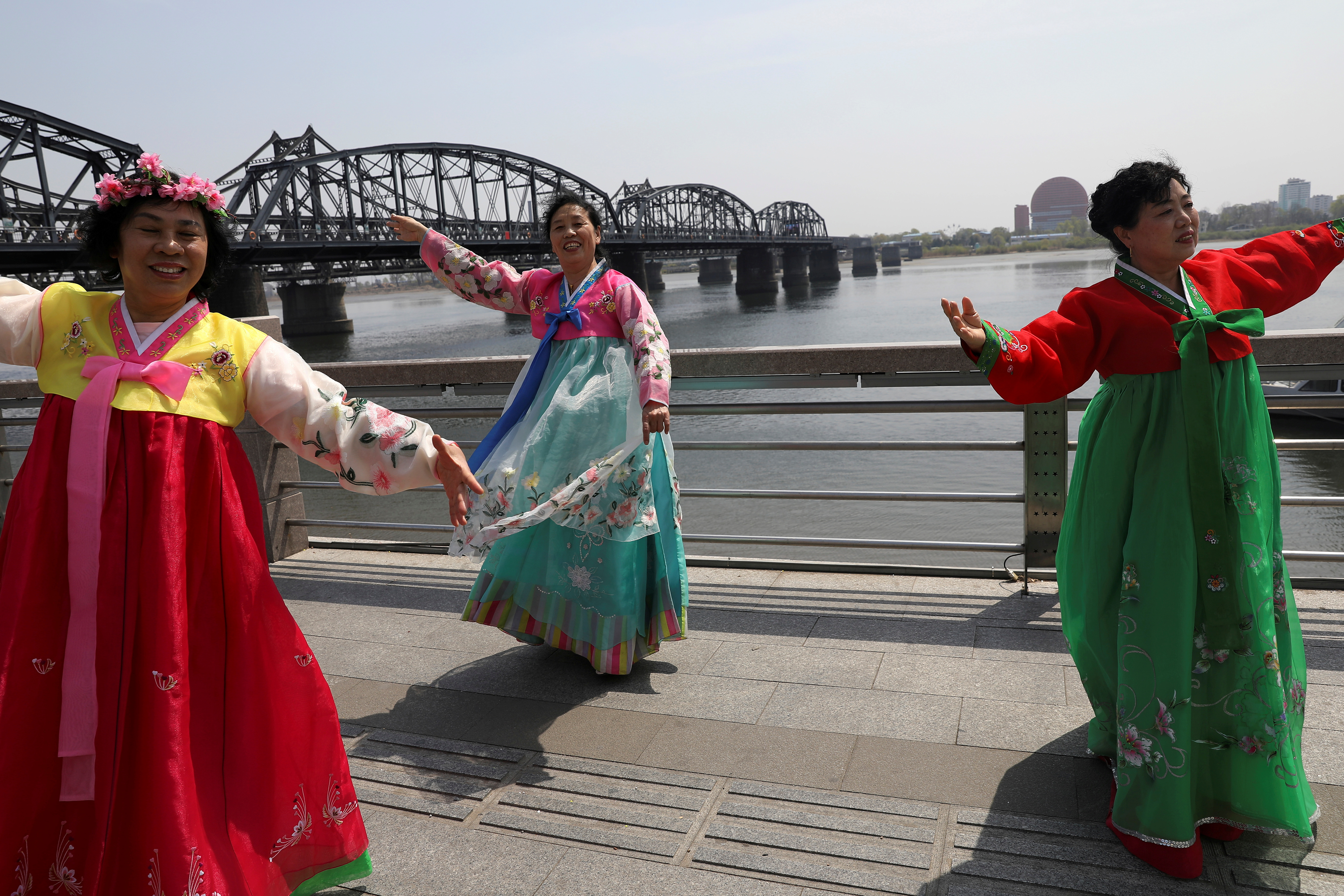 Tourists dressed in North Korean costumes dance as they pose for pictures near the Friendship Bridge and Broken Bridge over the Yalu River, which separates North Korea's Sinuiju from China, in Dandong, Liaoning province, China April 21, 2021. REUTERS/Tingshu Wang