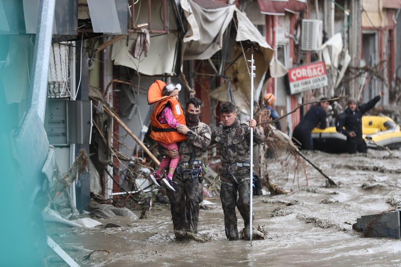 Paieškos ir gelbėjimo komandos nariai evakuoja mergaitę per staigius potvynius, apėmusius miestus Turkijos Juodosios jūros regione, Bozkurt mieste, Kastamonu provincijoje, Turkijoje, 12 m. Rugpjūčio 2021 d. Nuotrauka daryta 12 m. Rugpjūčio 2021 d. Vidaus nelaimių ir ekstremalių situacijų valdymo tarnybos (AFAD) atstovas spaudai/dalomoji medžiaga per REUTERS