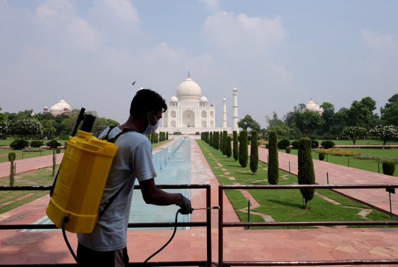 A man sanitizes railings in the premises of Taj Mahal after authorities reopened the monument to visitors, amidst the coronavirus disease (COVID-19) outbreak, in Agra, India, September 21, 2020. REUTERS/Alasdair Pal/File Photo