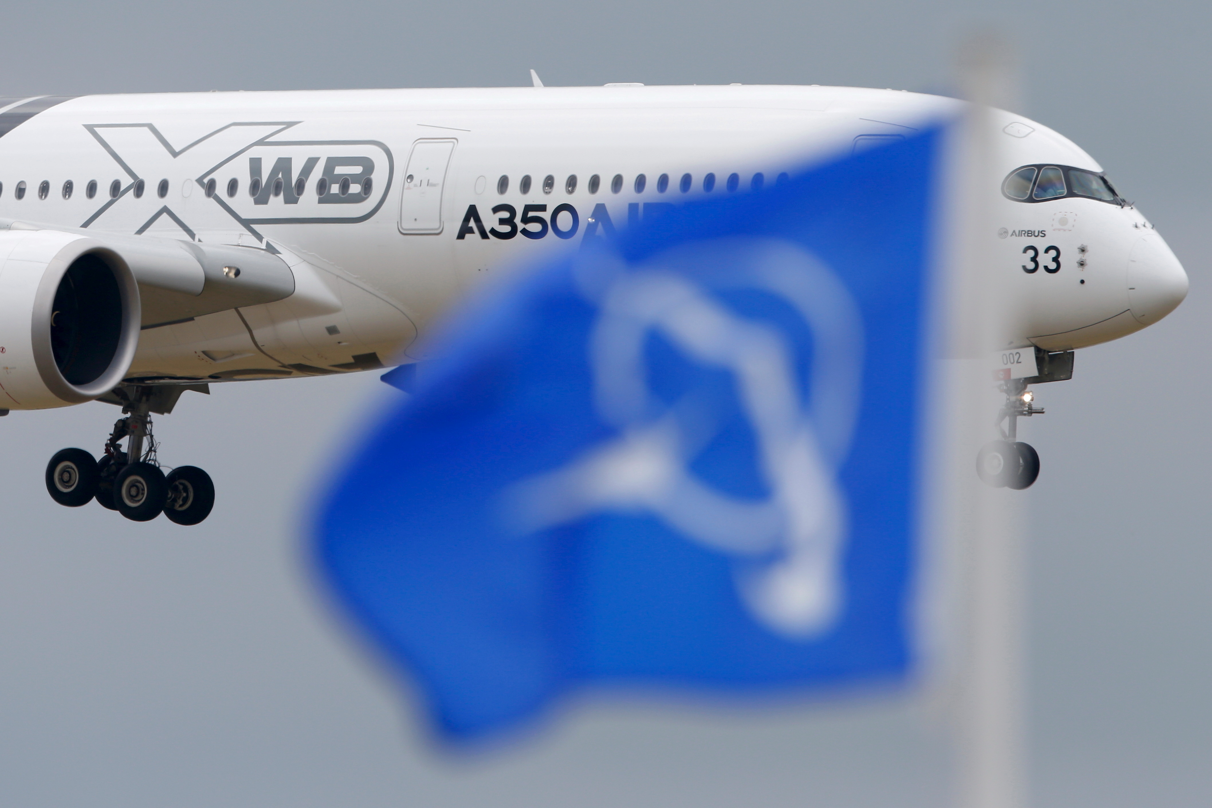 An Airbus A350 flies over a Boeing flag while landing after a flying display during the 51st Paris Air Show at Le Bourget airport near Paris, June 18, 2015.