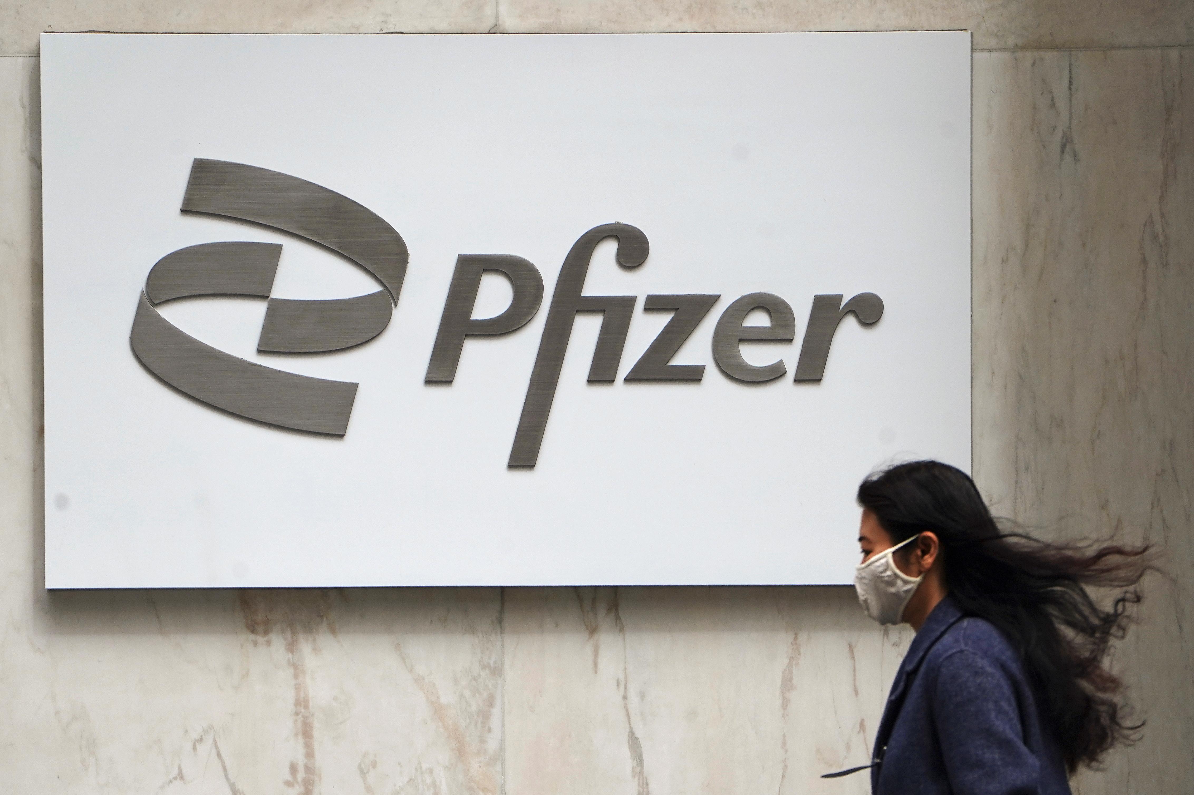 A person walks past a Pfizer logo amid the coronavirus disease (COVID-19) pandemic in the Manhattan borough of New York City, New York, U.S., April 1, 2021. REUTERS/Carlo Allegri