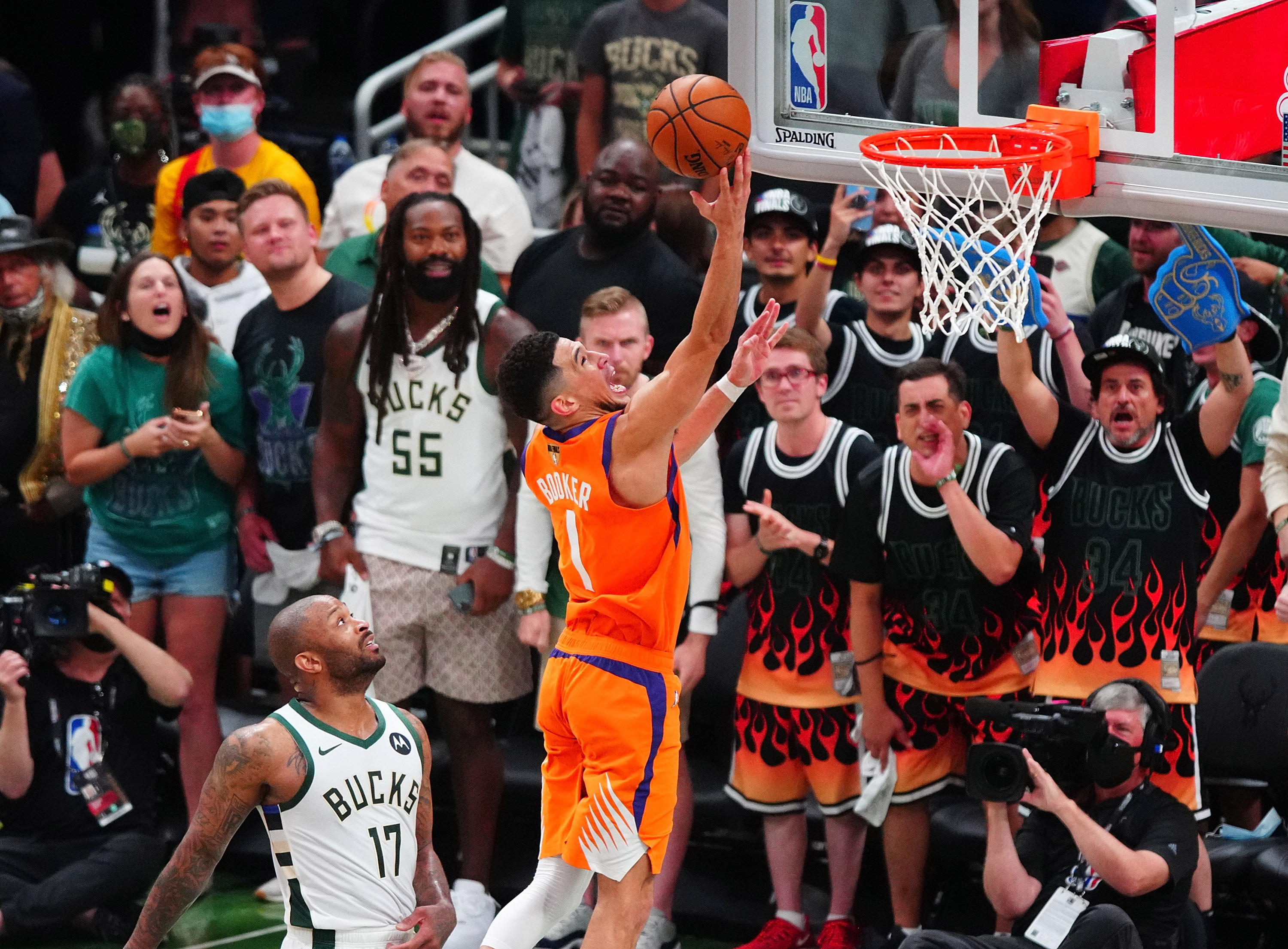 Jul 14, 2021; Milwaukee, Wisconsin, USA; Phoenix Suns guard Devin Booker (1) shoots in front of Milwaukee Bucks forward P.J. Tucker (17) during the fourth quarter in game four of the 2021 NBA Finals at Fiserv Forum. Mandatory Credit: Mark J. Rebilas-USA TODAY Sports