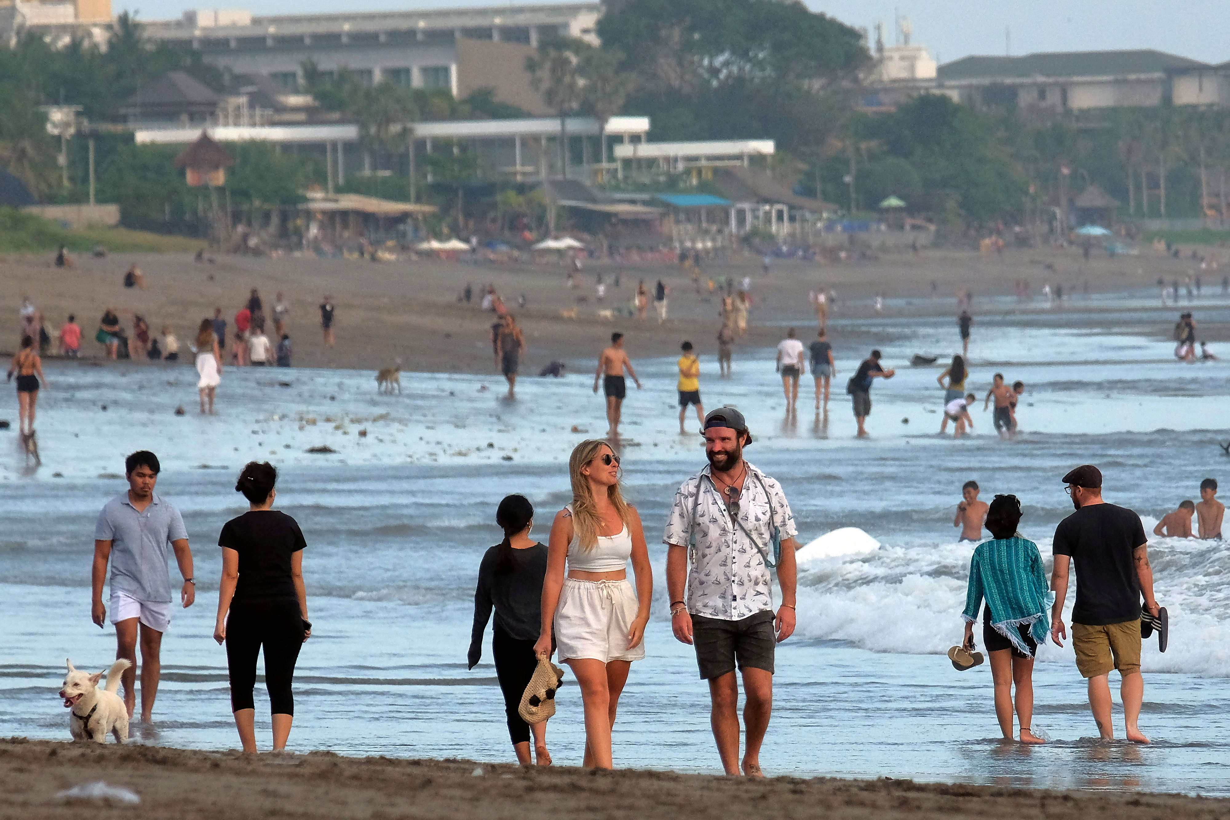 Tourists walk on a beach as the government extends restrictions to curb the spread of coronavirus disease (COVID-19) in Badung, Bali, Indonesia September 9, 2021. Antara Foto/Nyoman Hendra Wibowo/via REUTERS