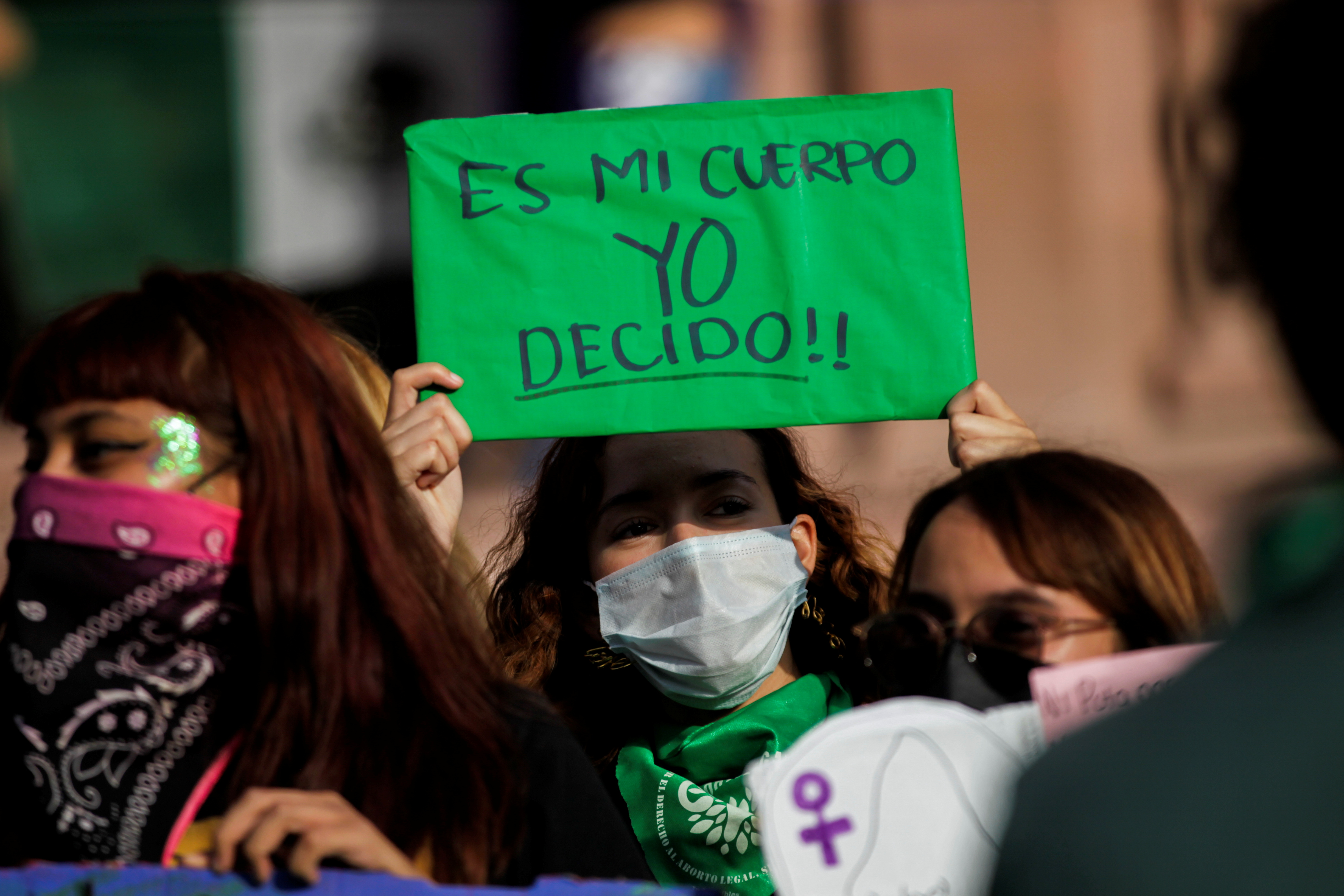 A woman holds up a banner which reads