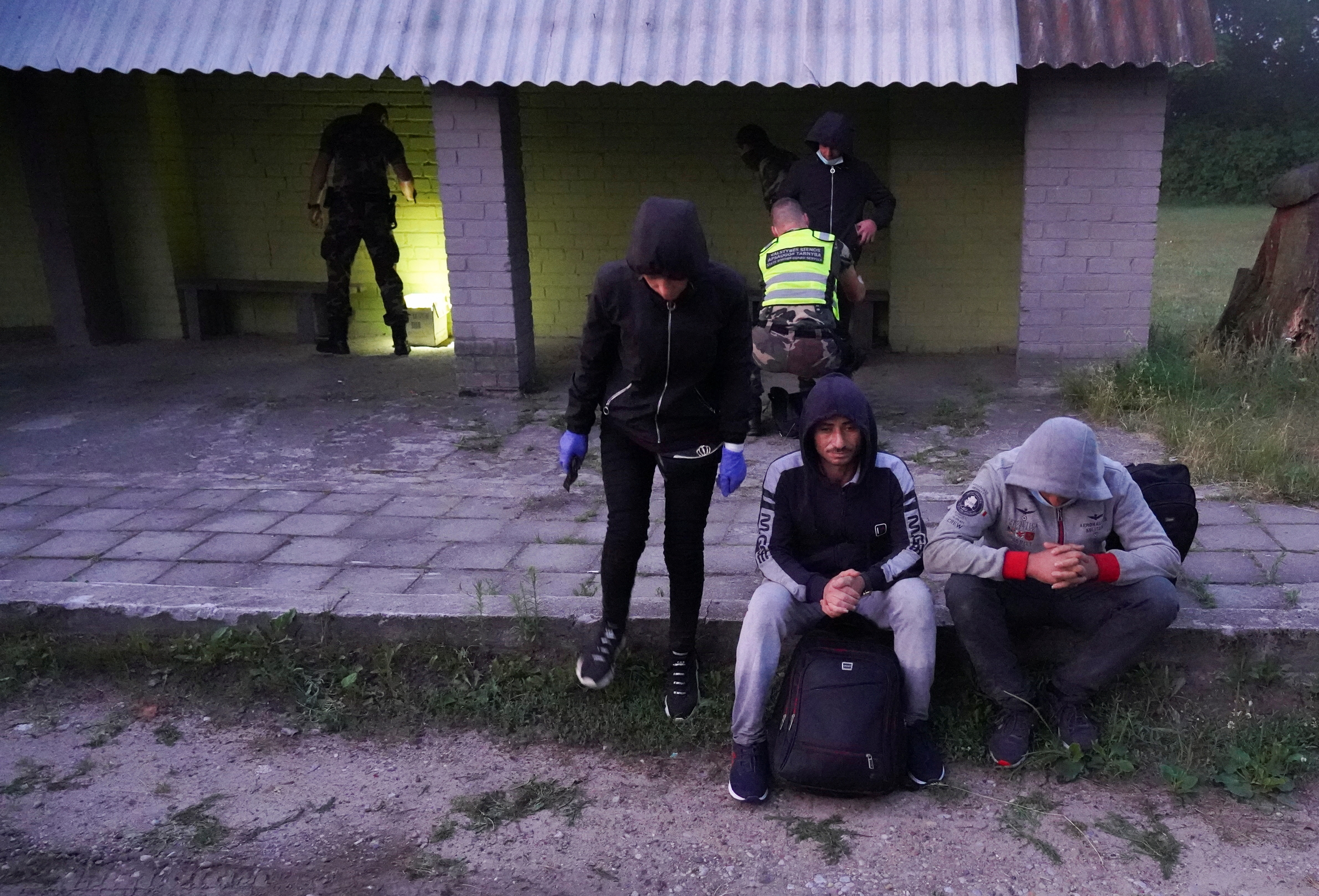 Lithuanian border guards detain migrants on Lithuania-Belarus border in Kalviai, Lithuania, July 7, 2021. REUTERS/Janis Laizans