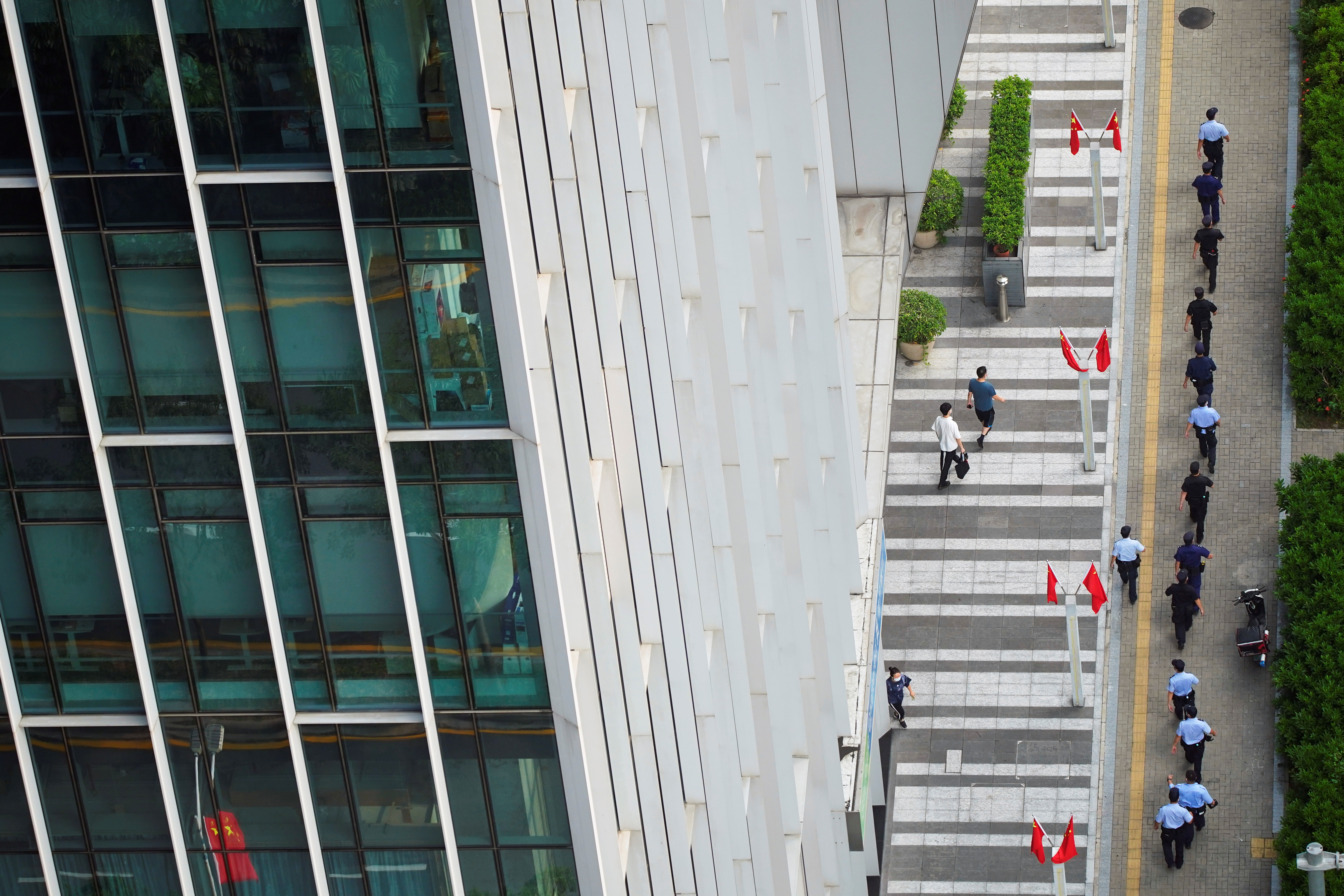 Police officers and security personnel walk outside the headquarters of China Evergrande Group in Shenzhen, Guangdong province, China, September 30, 2021. REUTERS/Aly Song