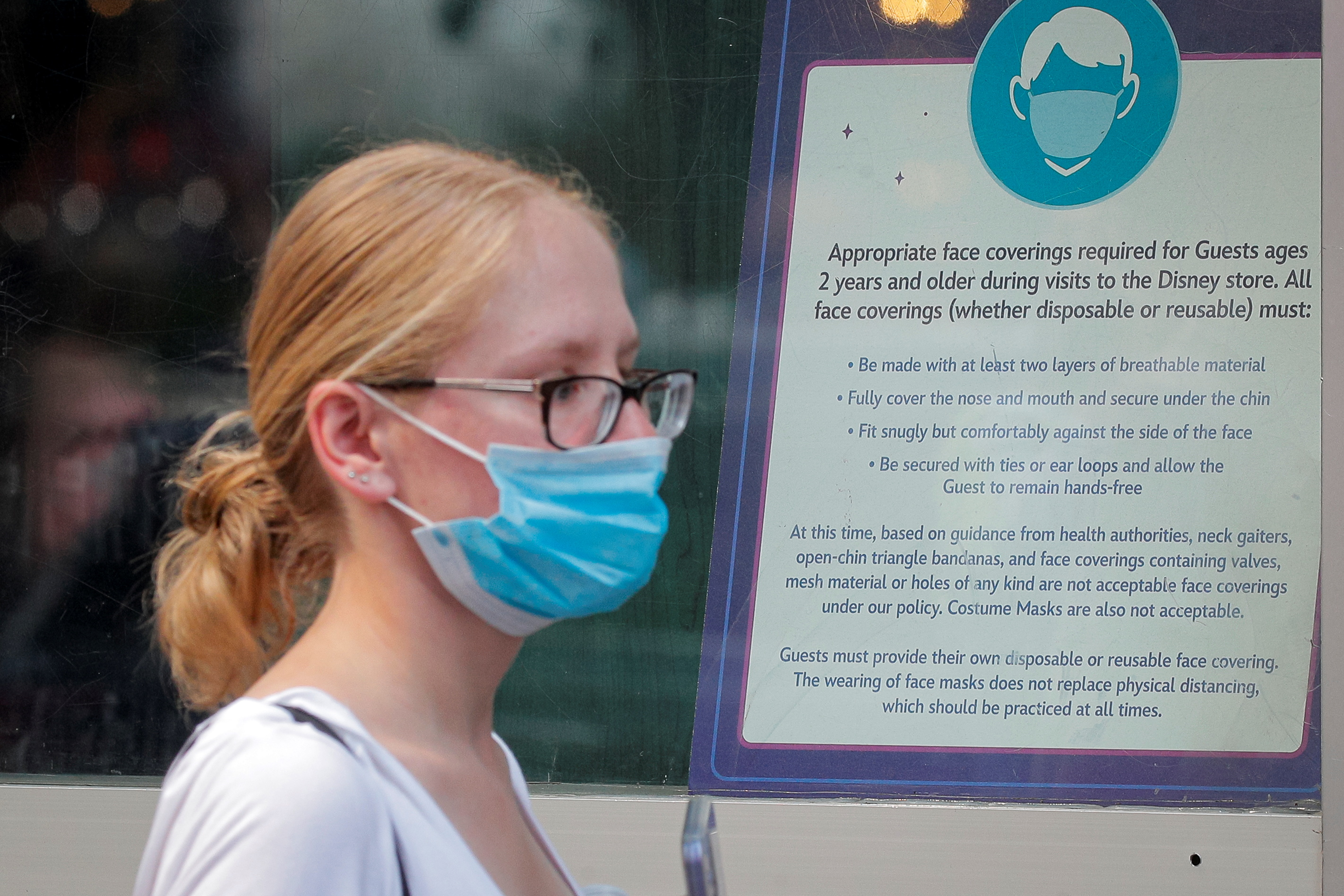 A woman wears a mask against the coronavirus disease (COVID-19), following the CDC recommendation that fully vaccinated Americans wear masks as the highly transmissible Delta variant has led to a surge in infections, as she enters the Disney Store in Times Square in New York City, New York, U.S., July 27, 2021. REUTERS/Brendan McDermid